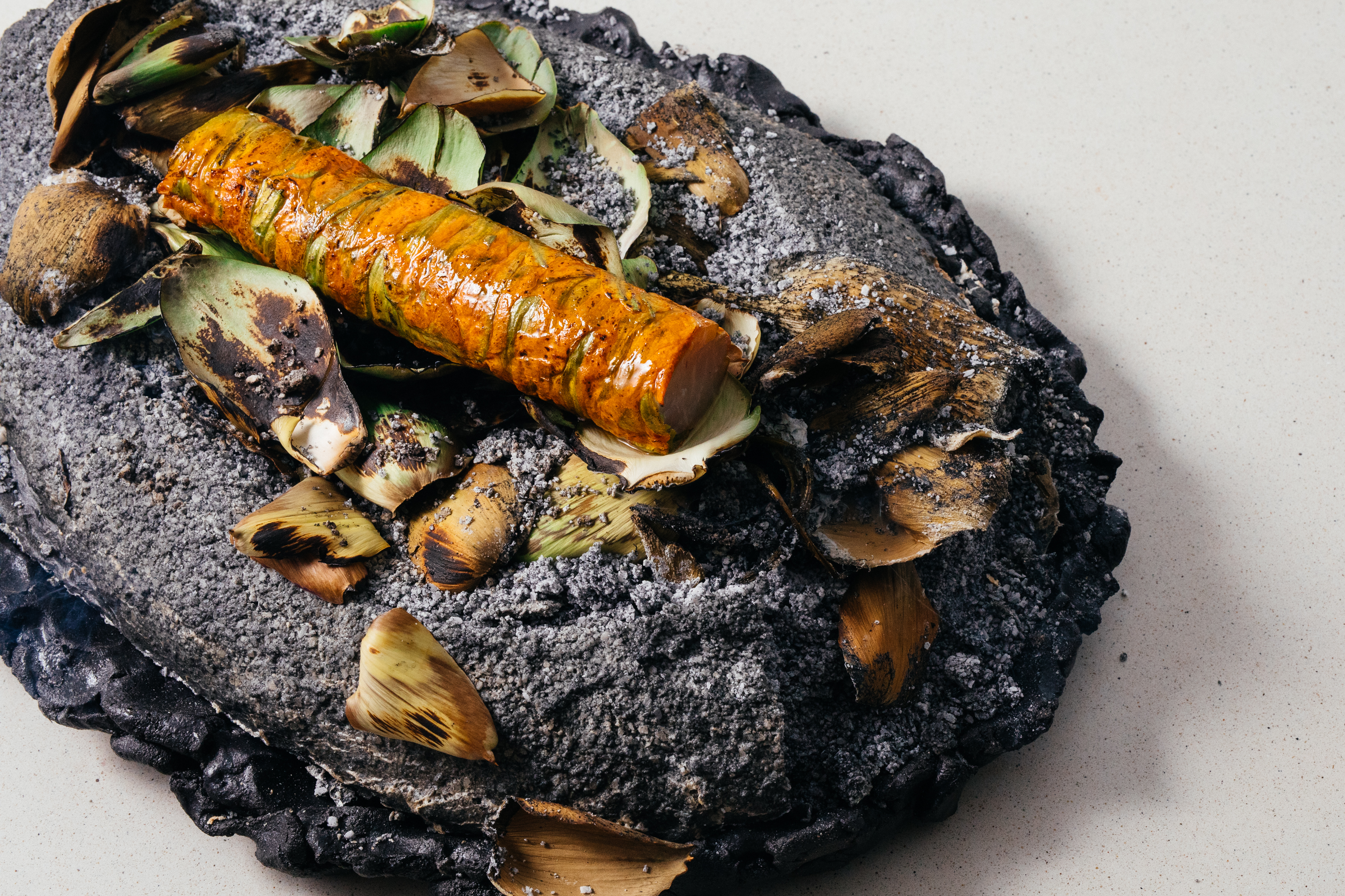 Sable fish wrapped in squash blossoms and salt baked. The salt bake is seasoned with roasted artichoke leaves.