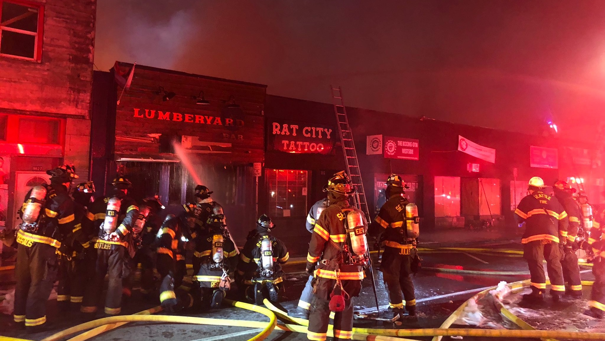 Firefighters work to control a blaze at night in fron of the Lumber Yard Bar and Rat City Tattoo in White Center