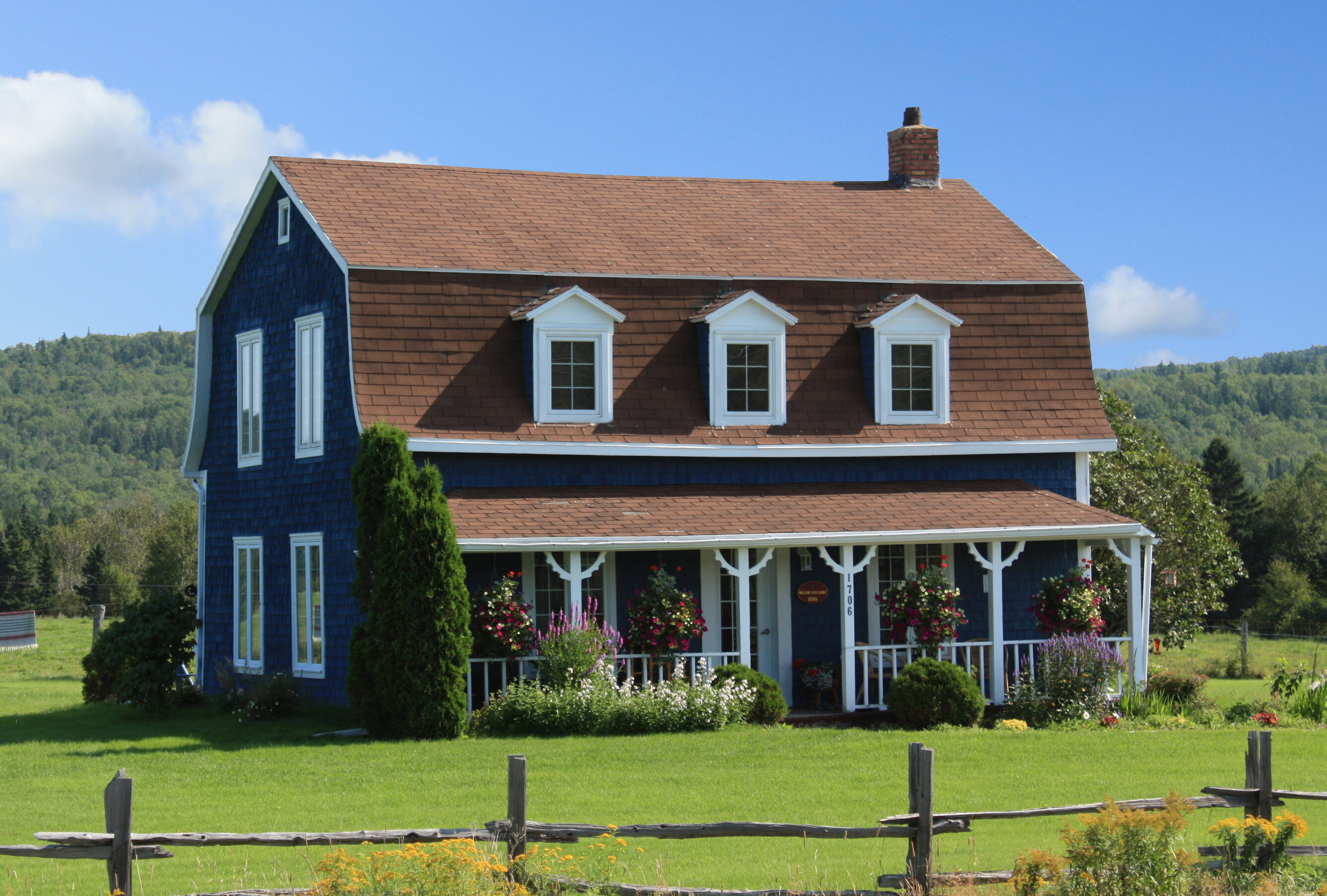 A navy blue farmhouse on a large, secluded piece of property.