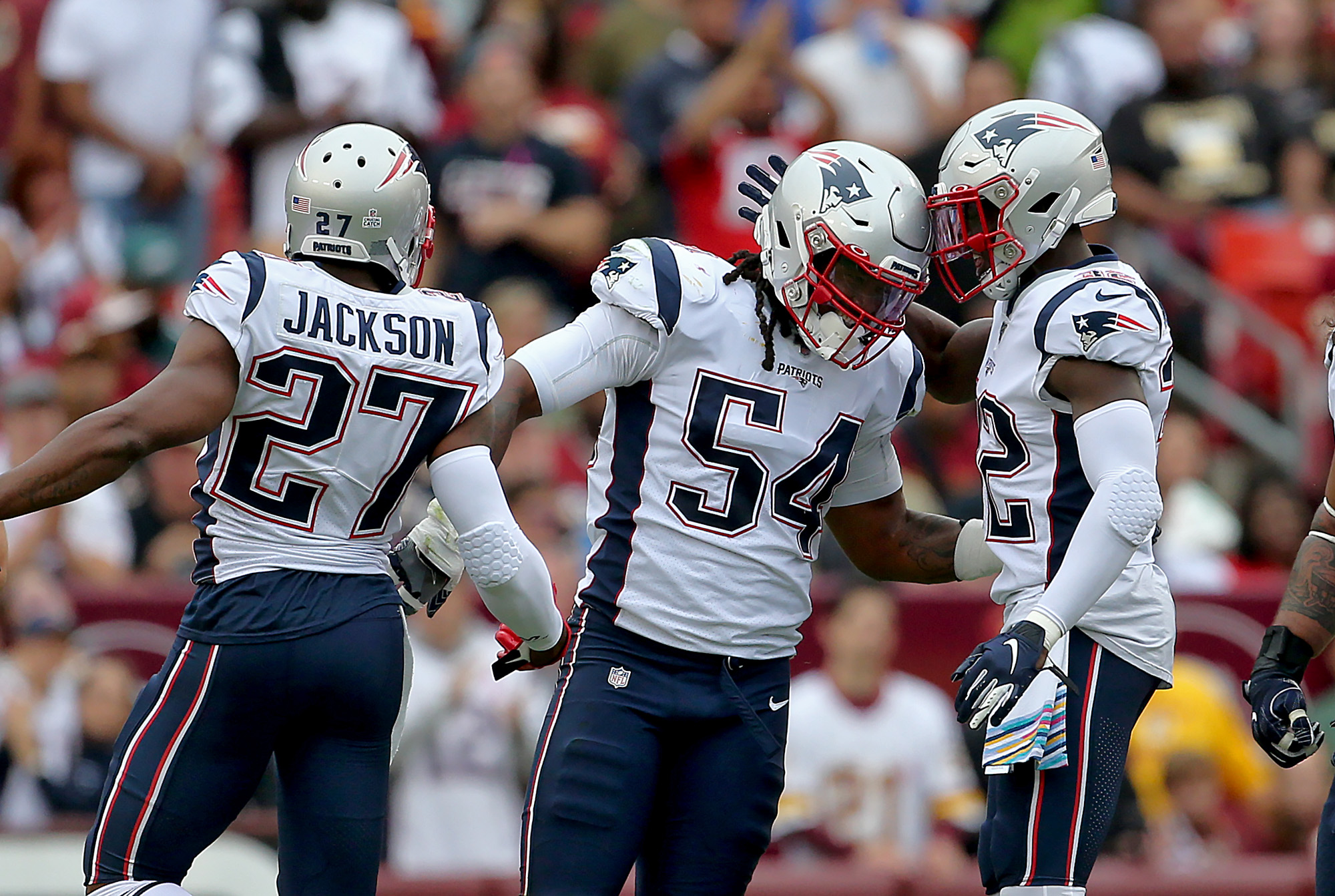 LANDOVER MD. - OCTOBER 6: New England Patriots' Dont'a Hightower celebrates with J.C. Jackson and Devin McCourty after sacking Washington Redskins quarterback Colt McCoy for a loss of 6 yards during the 2nd quarter of the game at FedEx Field on October 6,