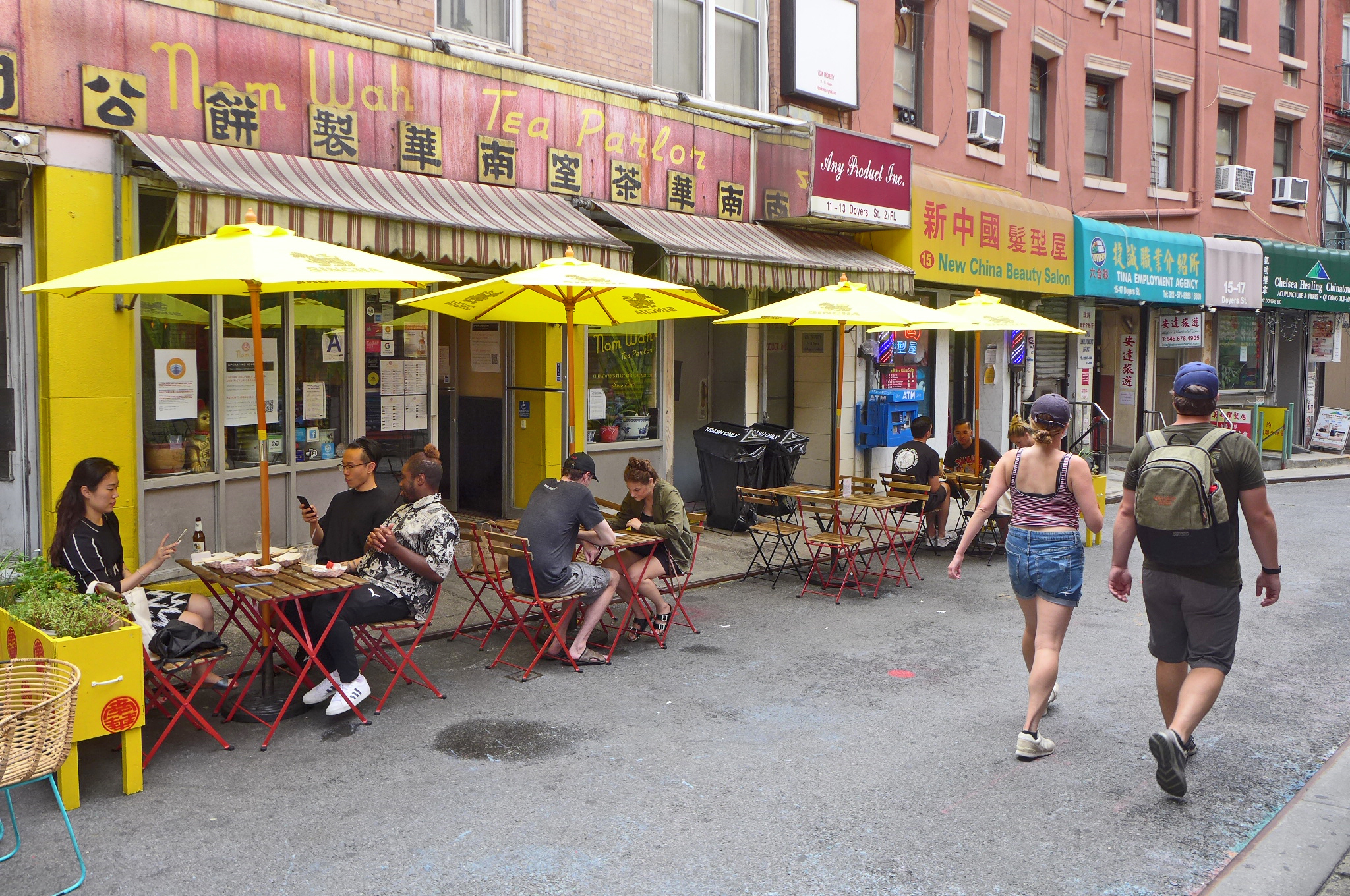 A restaurant with a faded sign and tables set out in front under yellow umbrellas.