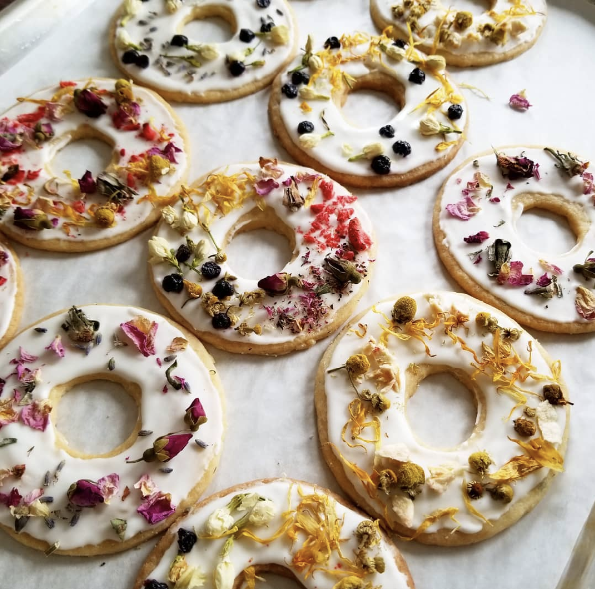 several ring cookies with white icing and multicolored flowers on top