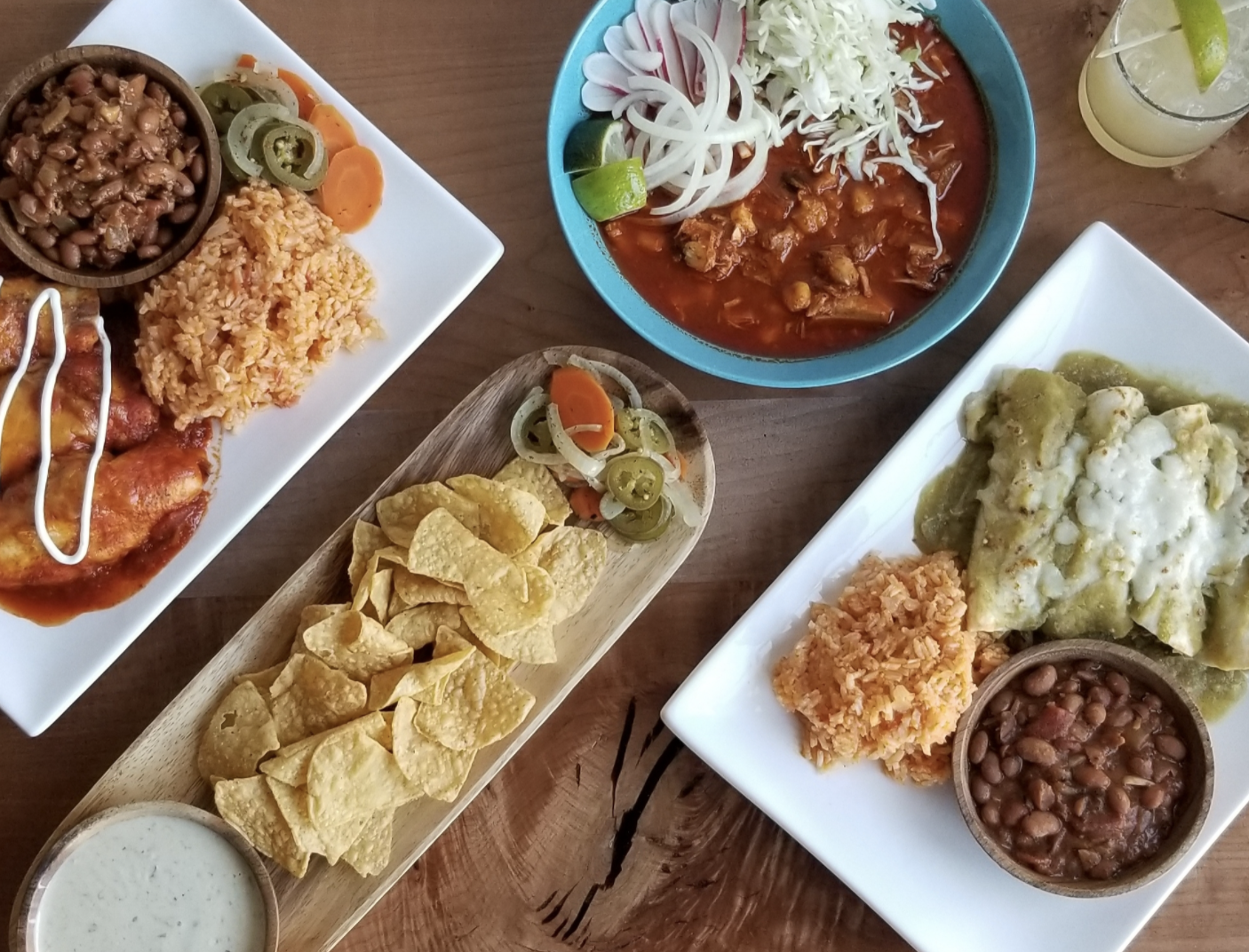 A topdown view of Tex Mex dishes, including enchiladas, chili, and chips with a side of dipping sauce