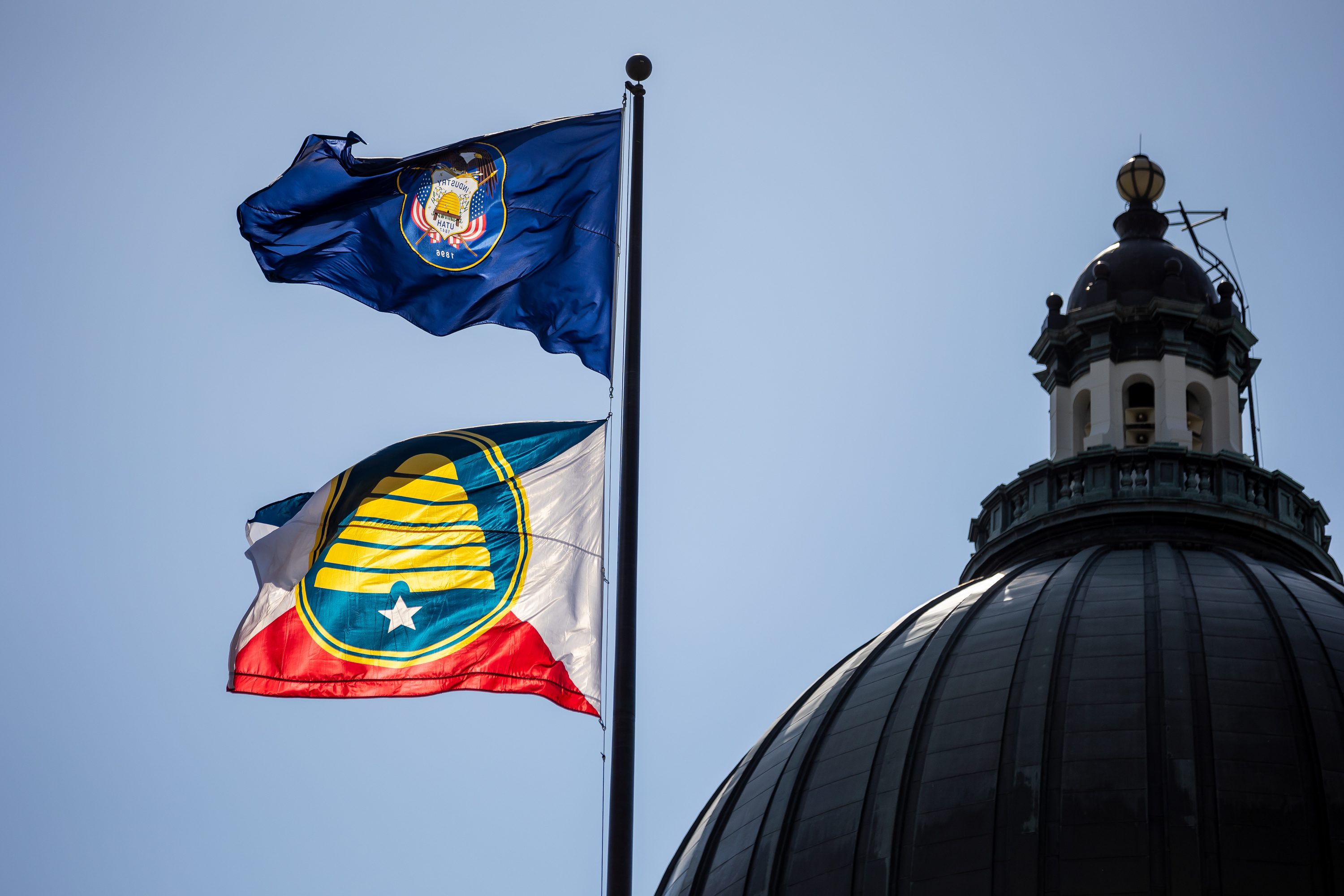 The Utah state flag, top, and the new commemorative state flag, below, fly atop the Capitol in Salt Lake City on Tuesday, July 13, 2021.