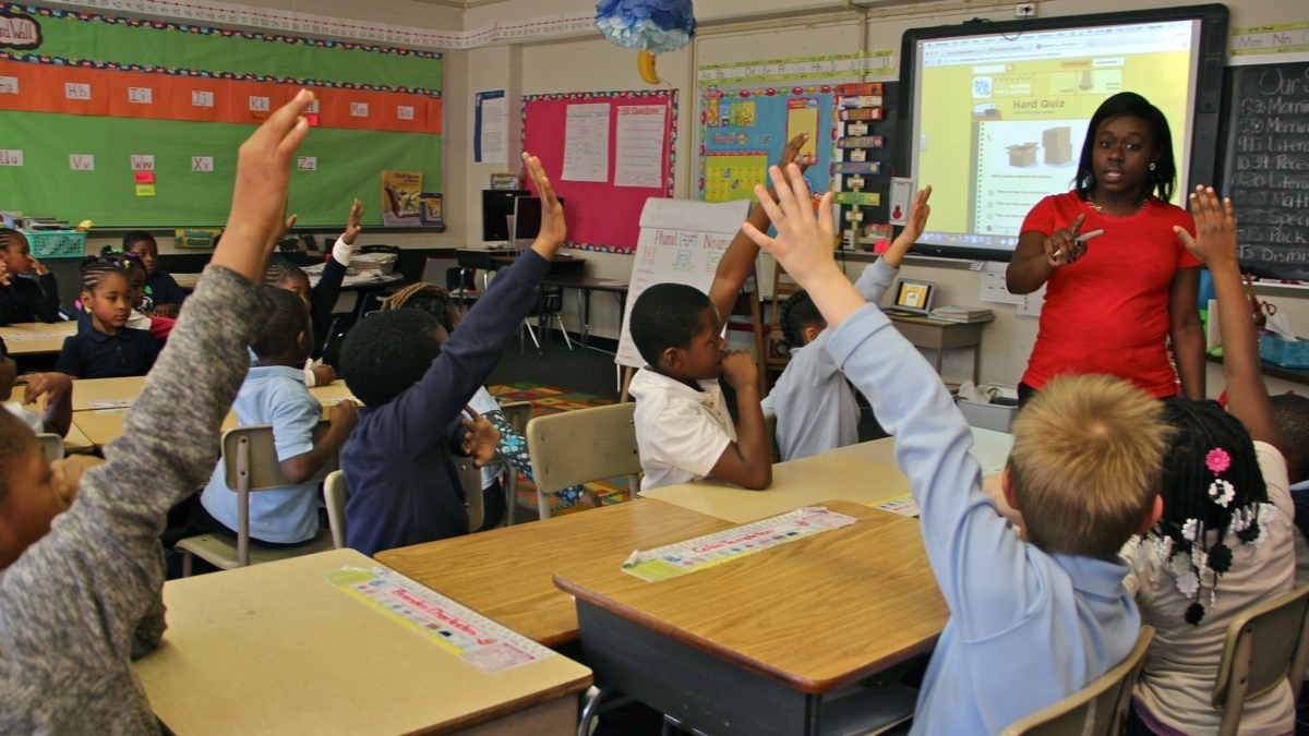 Students raise their hands at their desks while a teacher points to them at the front of the classroom.