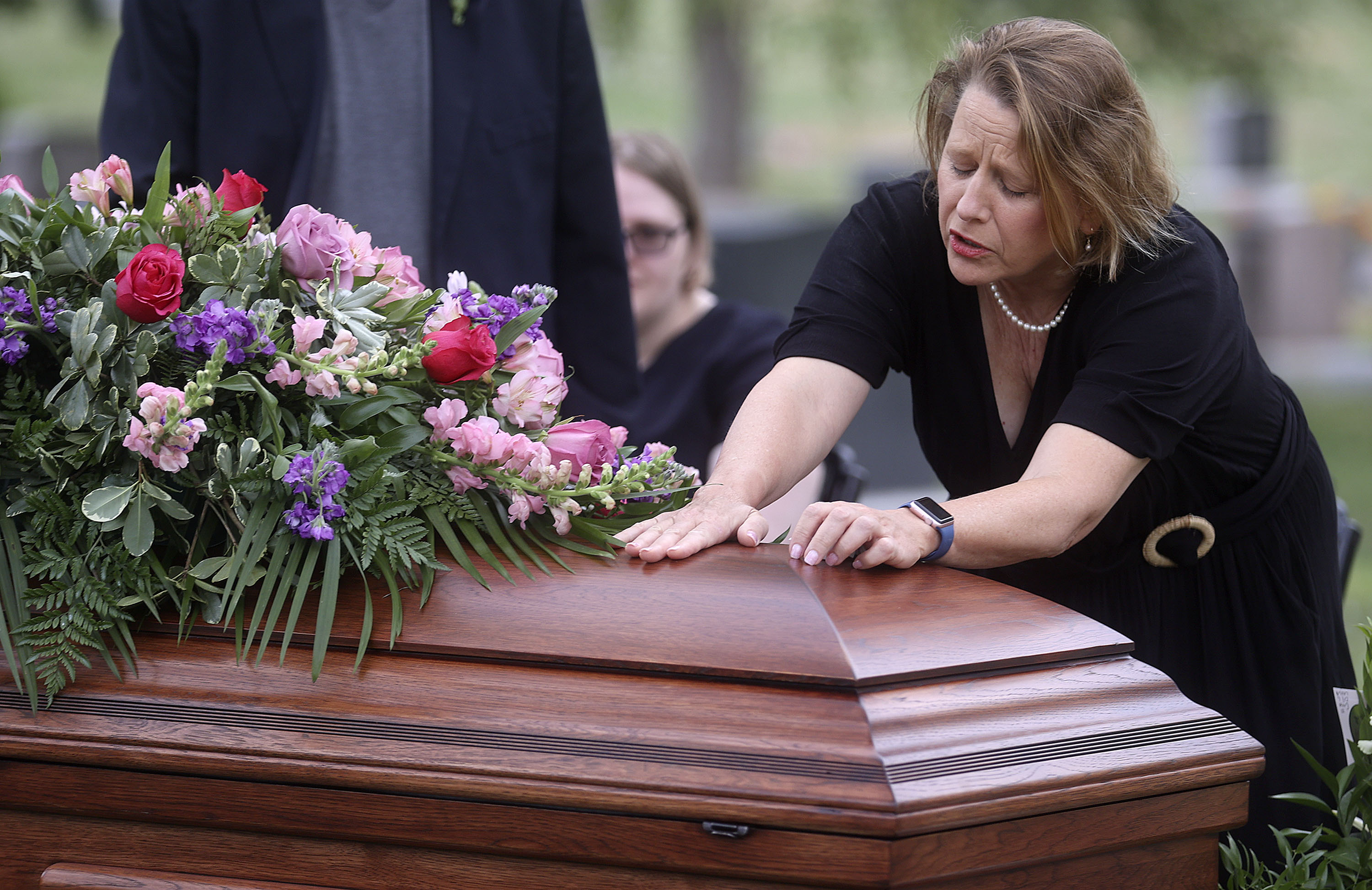 Tricia Wright grieves over the casket of her sister, Shawna Wright, who died of heat exhaustion while homeless, during ShawnaWright's interment at Mount Olivet Cemetery in Salt Lake City on Tuesday, July 13, 2021.