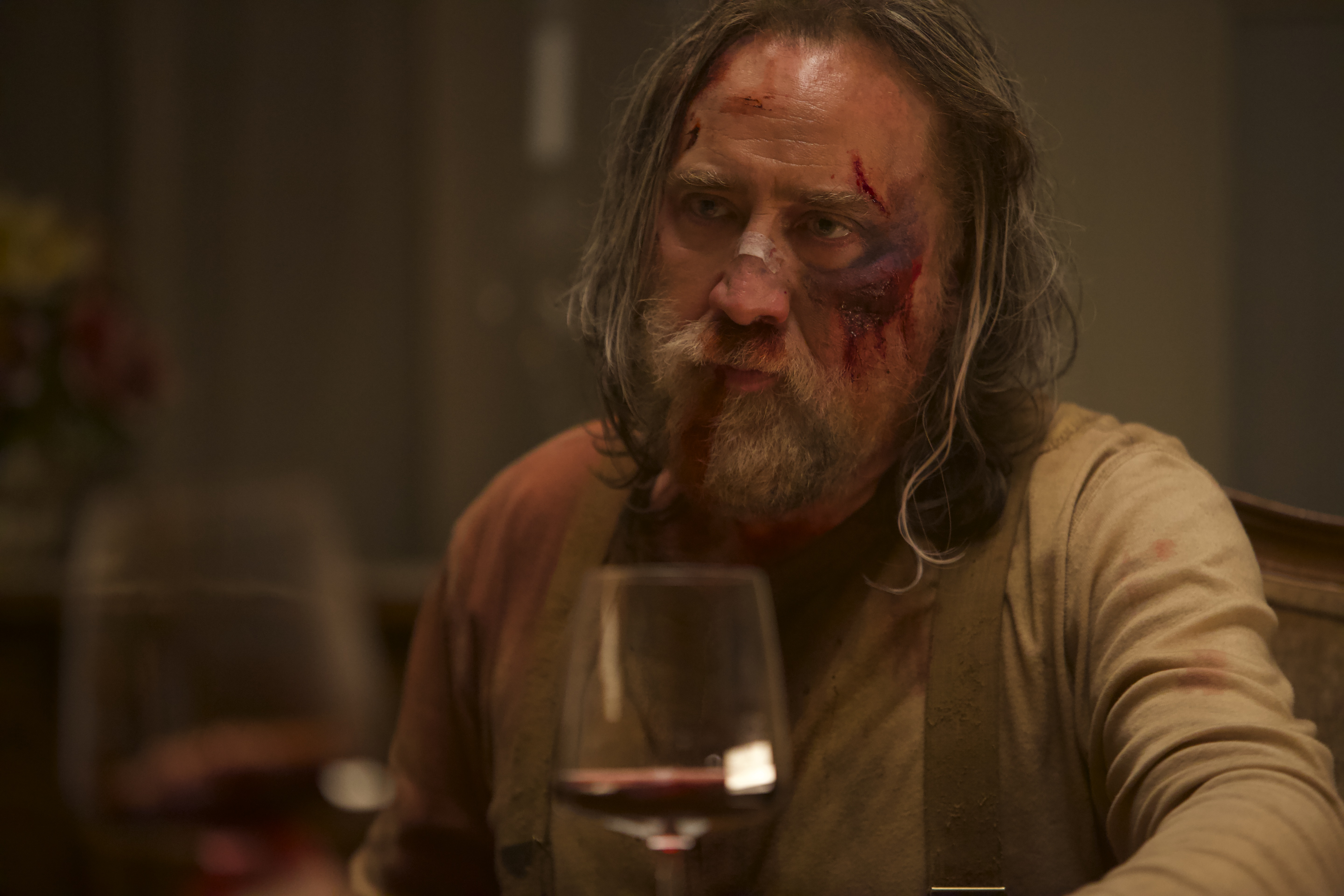 Nicolas Cage sits with a glass of wine in a still from the movie 'Pig.'