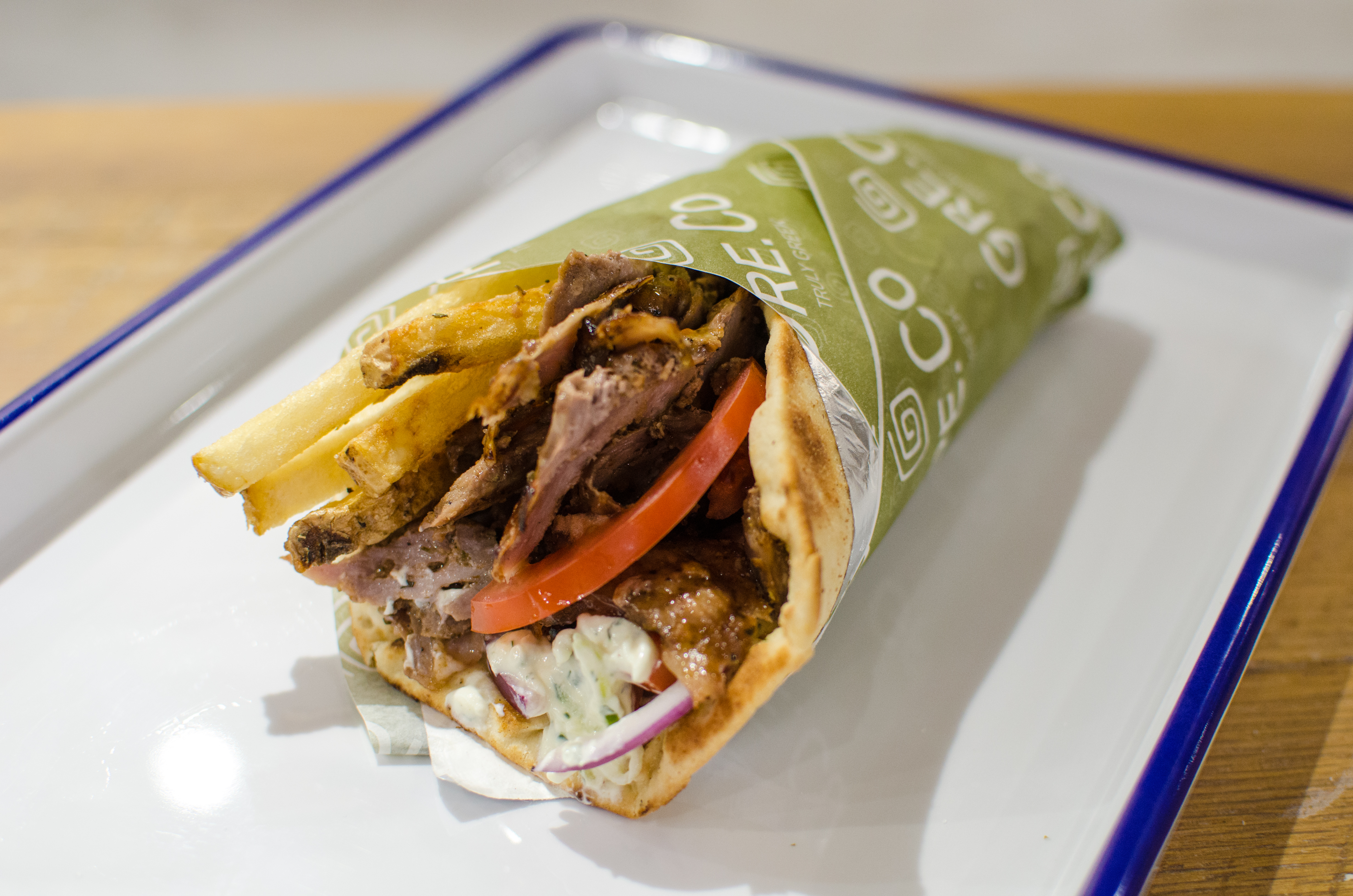 A gyro from fast-casual joint GRECO bursts with veggies, meat, and French fries