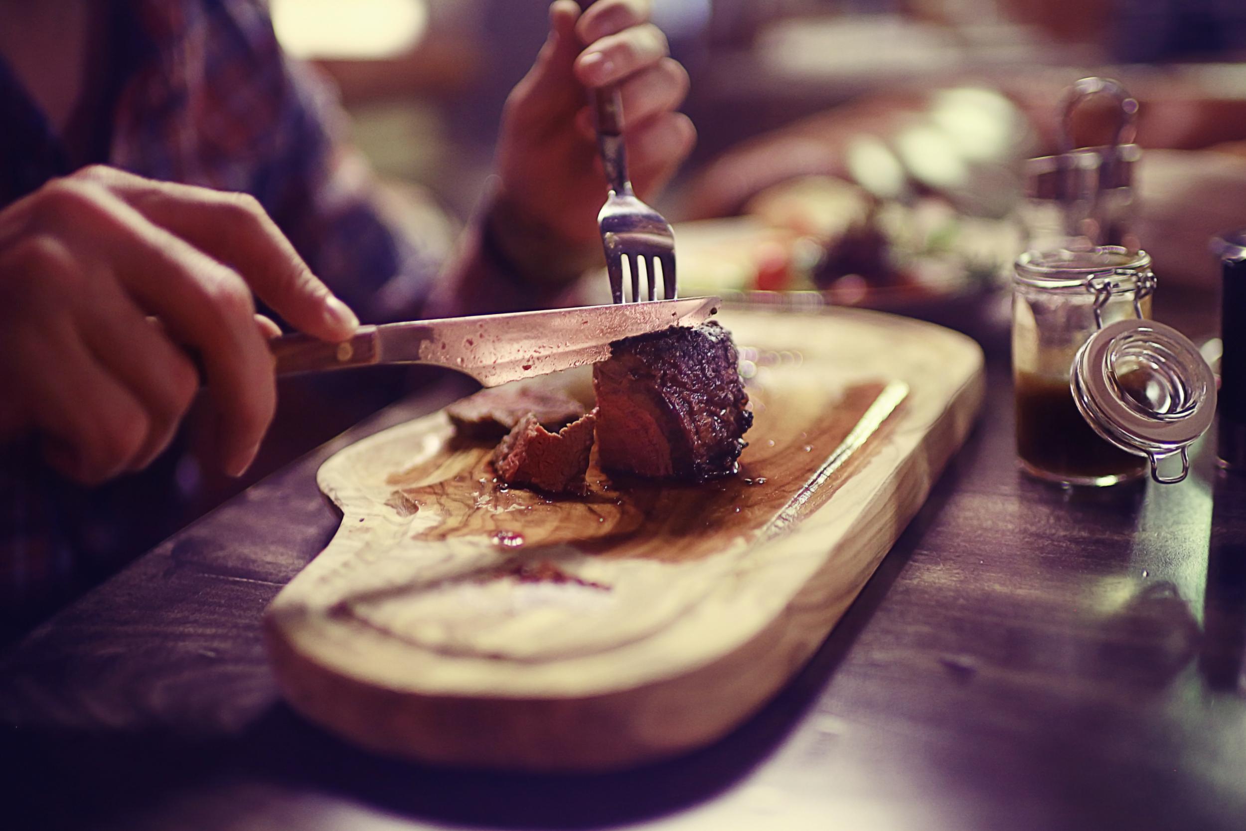 A hand cutting a steak