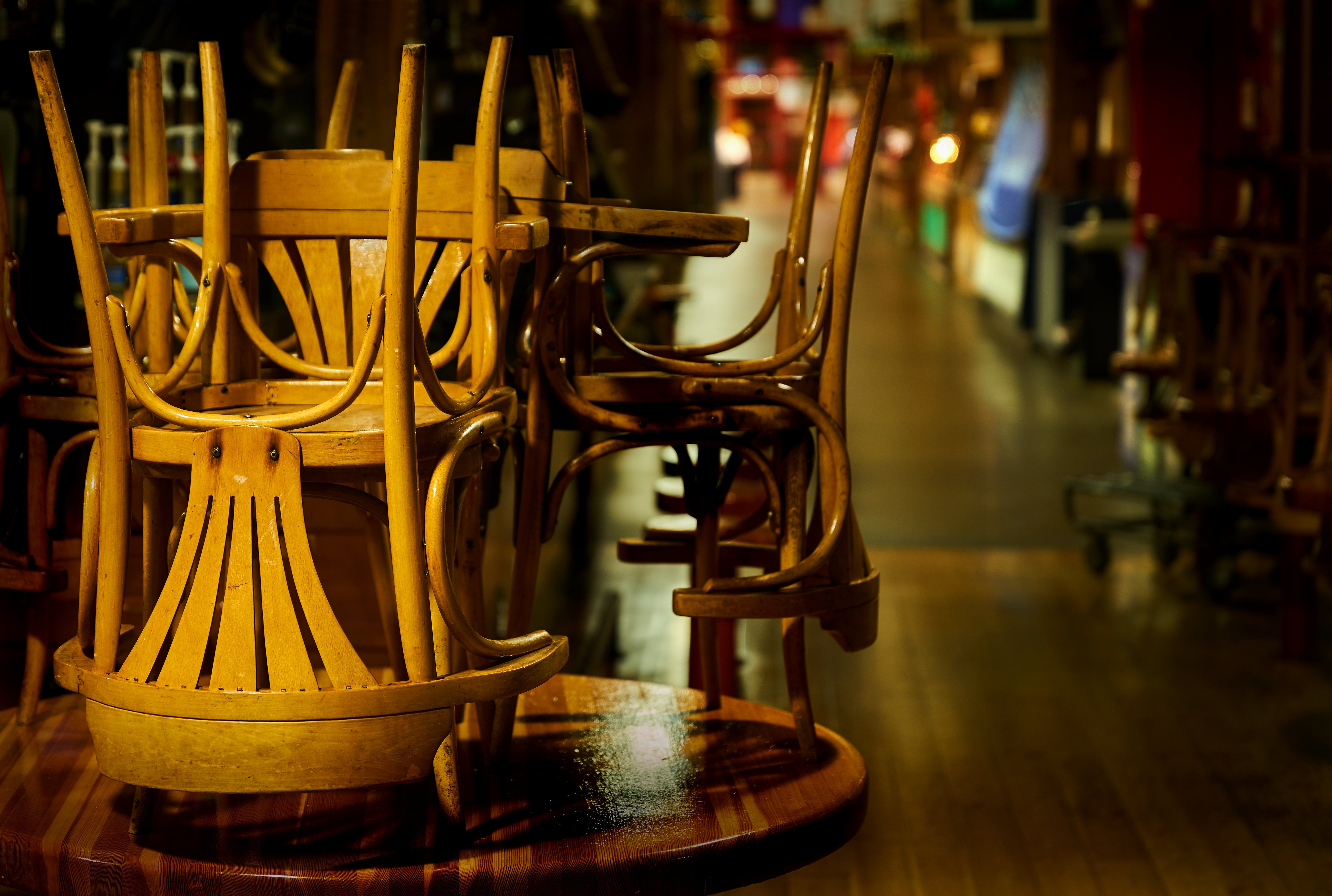 Light wood dining chairs stacked on tables in a dark restaurant.