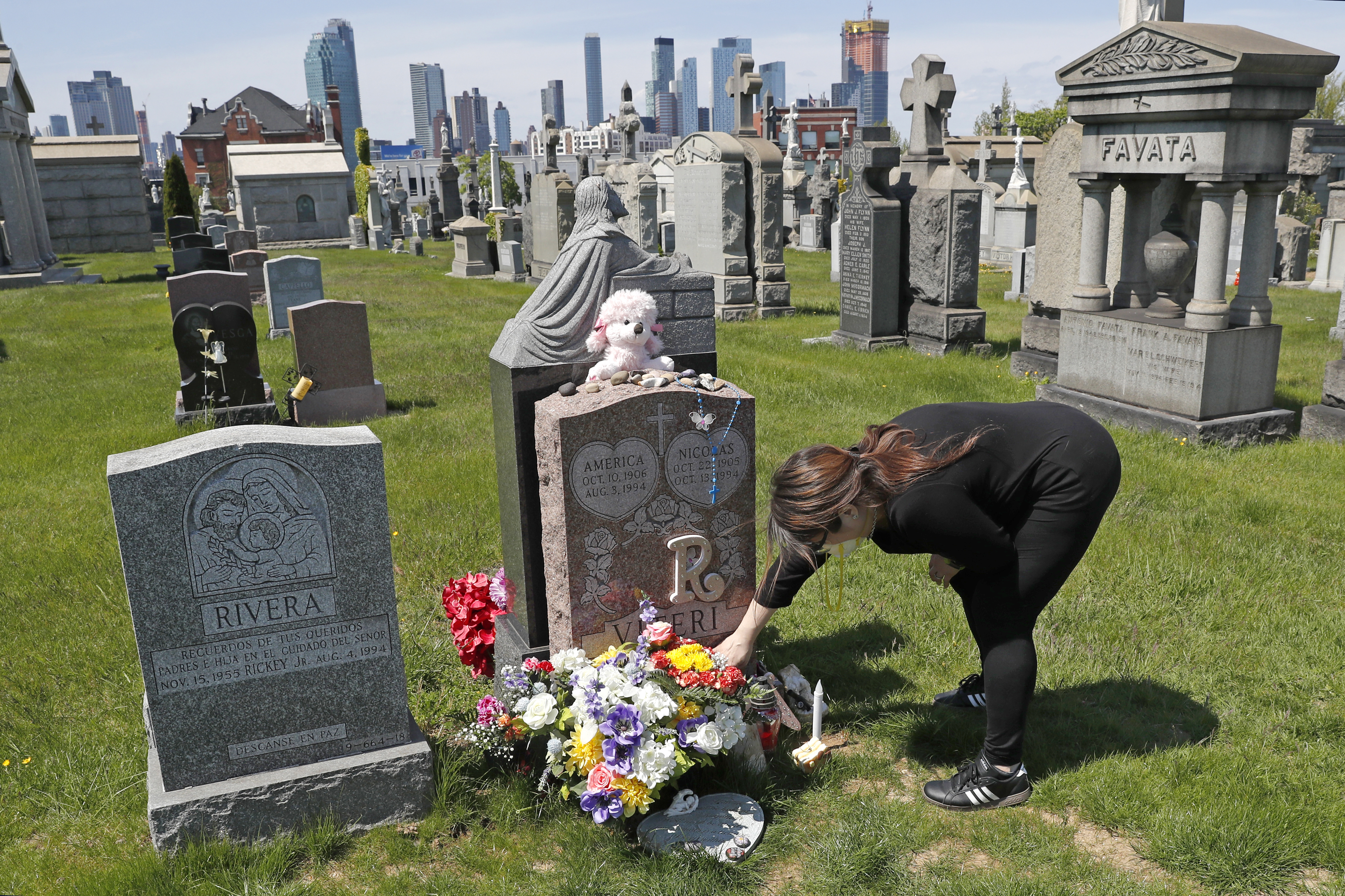In this Sunday, May 10, 2020 file photo, Sharon Rivera adjusts flowers and other items left at the grave of her daughter, Victoria, at Calvary Cemetery in New York, on Mother's Day. Victoria died of a drug overdose in Sept. 22, 2019, when she just 21 years old.