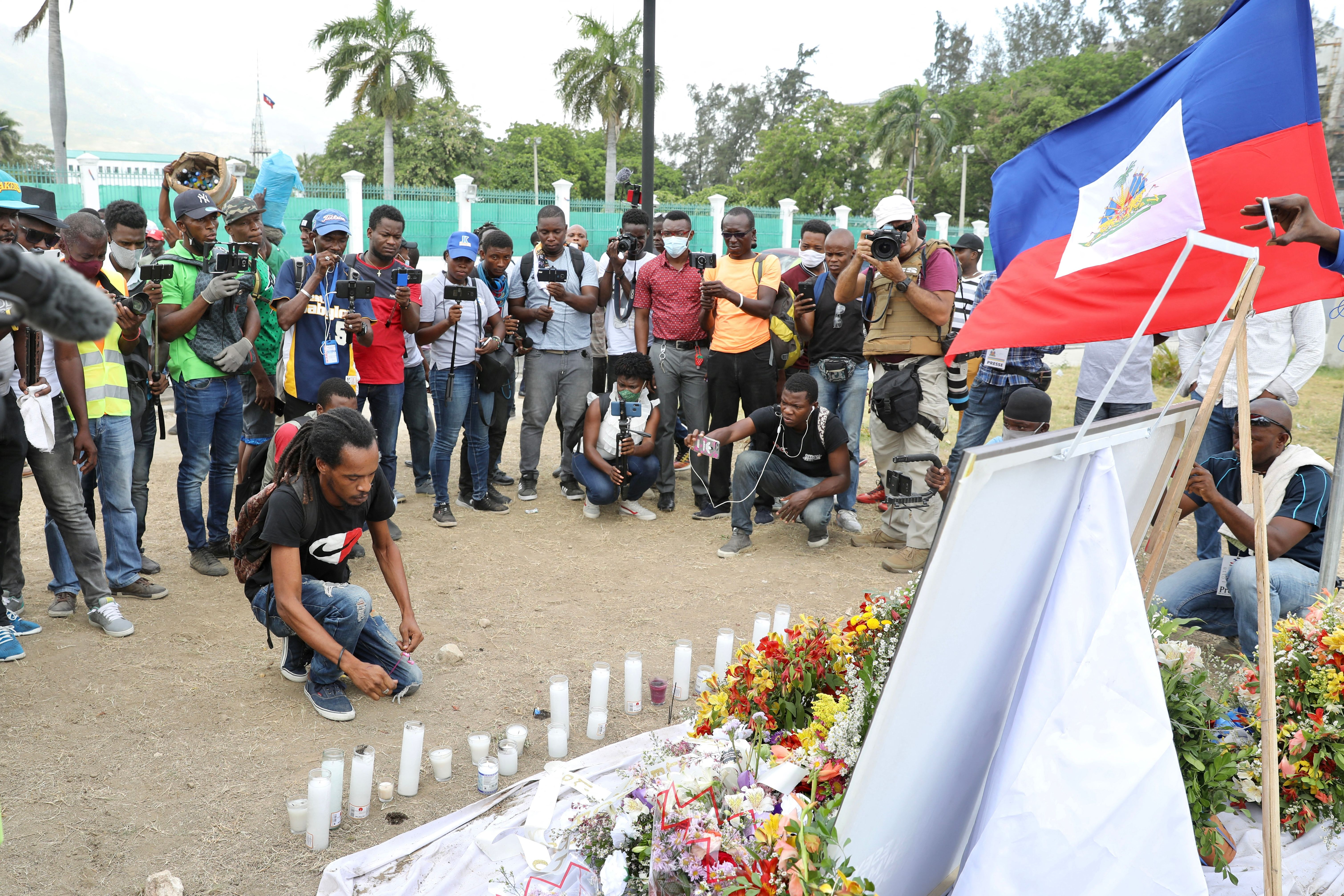 A crowd of people is gathered to pay their respects following the assassination of Haitian President Jovenel Moise on July 14, 2021. One man is kneeling in front of a vigil with candles, flowers, a photo of the late president, and a Haitian flag.
