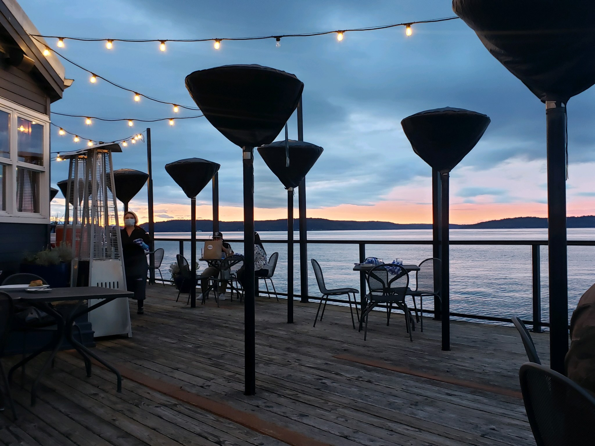 A view of the sound from Duke's Chowder House in West Seattle, with a masked server and tables on the patio