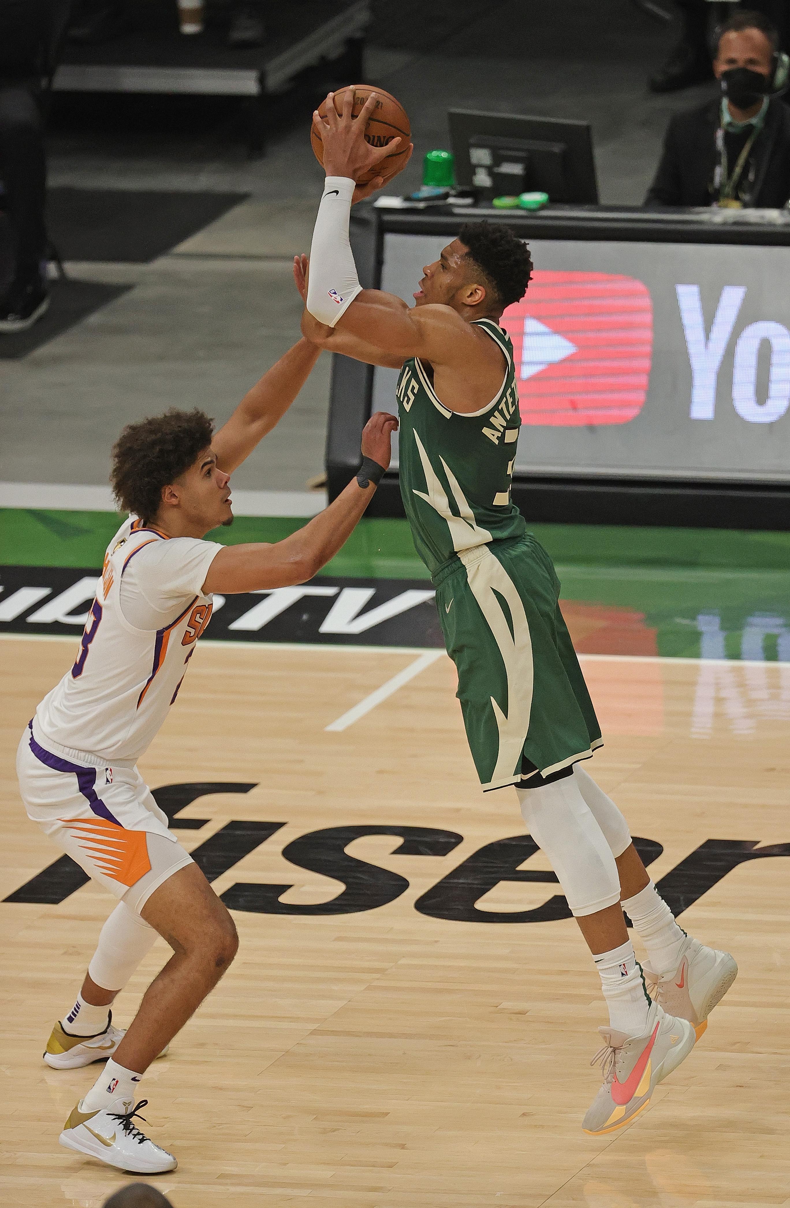 Giannis Antetokounmpo #34 of the Milwaukee Bucks shoots over Cameron Johnson #23 of the Phoenix Suns at Fiserv Forum on July 11, 2021 in Milwaukee, Wisconsin. The Bucks defeated the Suns 120-100.