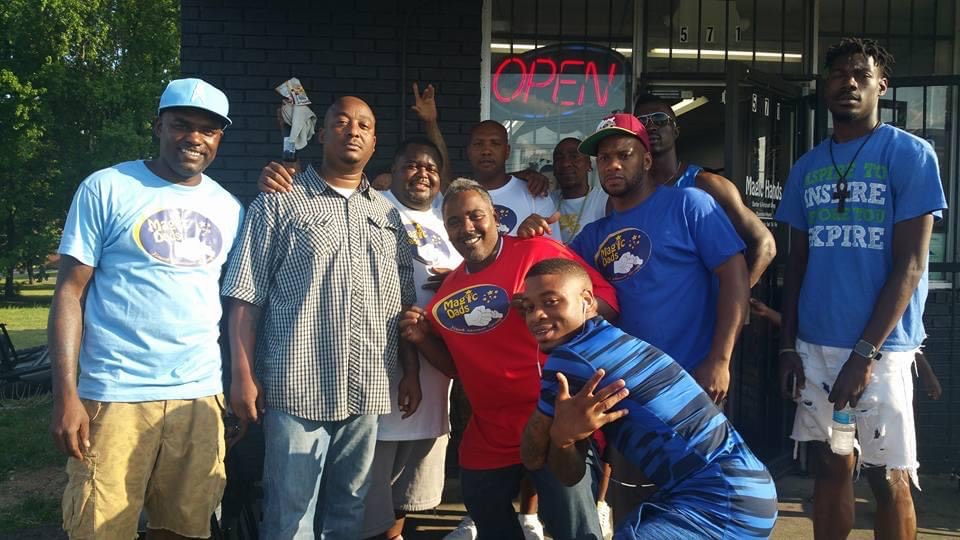 A group of men with Magic Dads mentoring group gather together cheerfully on the sidewalk for a photo.