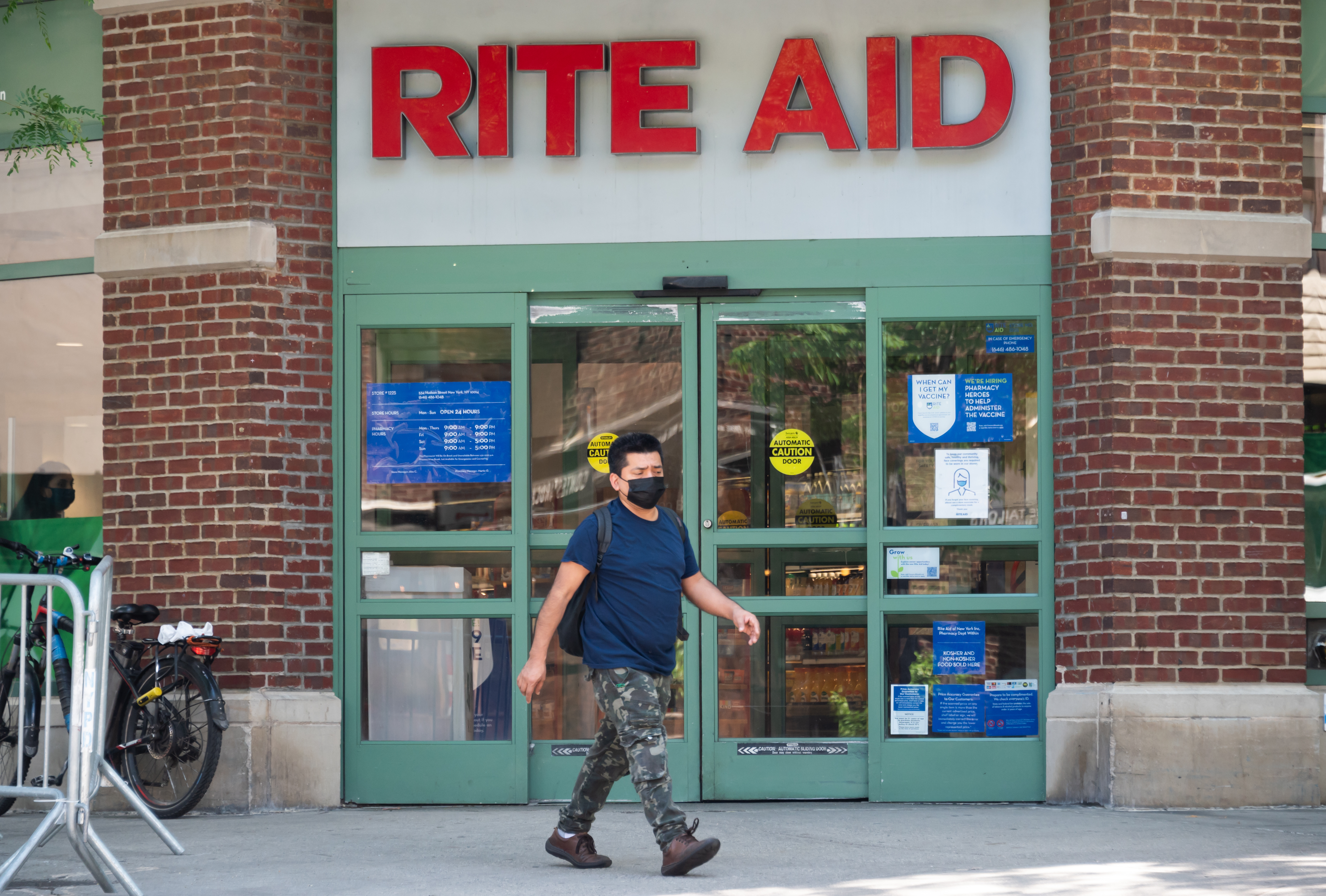 A masked person walks in front of a Rite Aid.