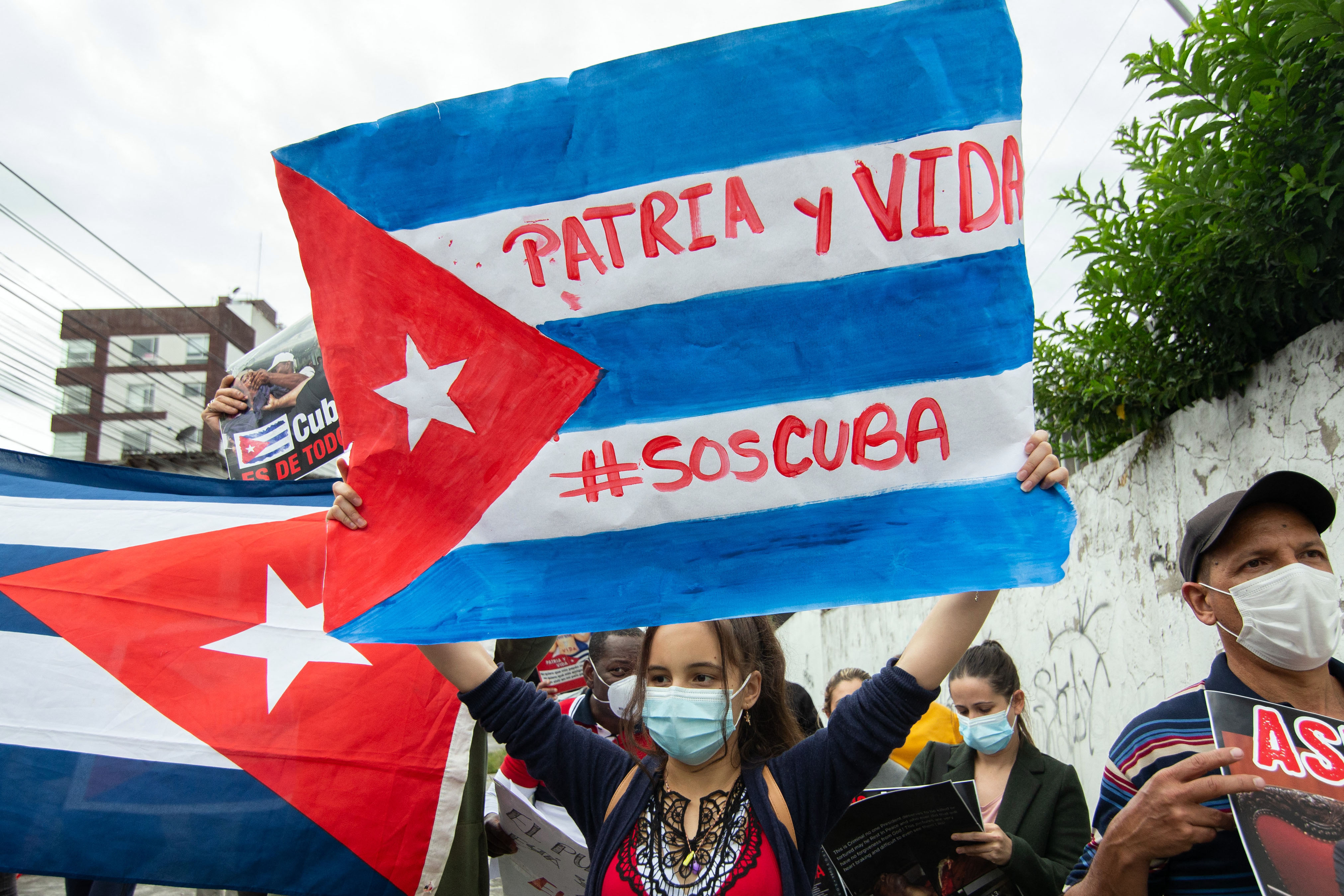 """A protester holds up a hand-drawn Cuban flag sign that reads """"Patria y vida, SOS Cuba."""""""