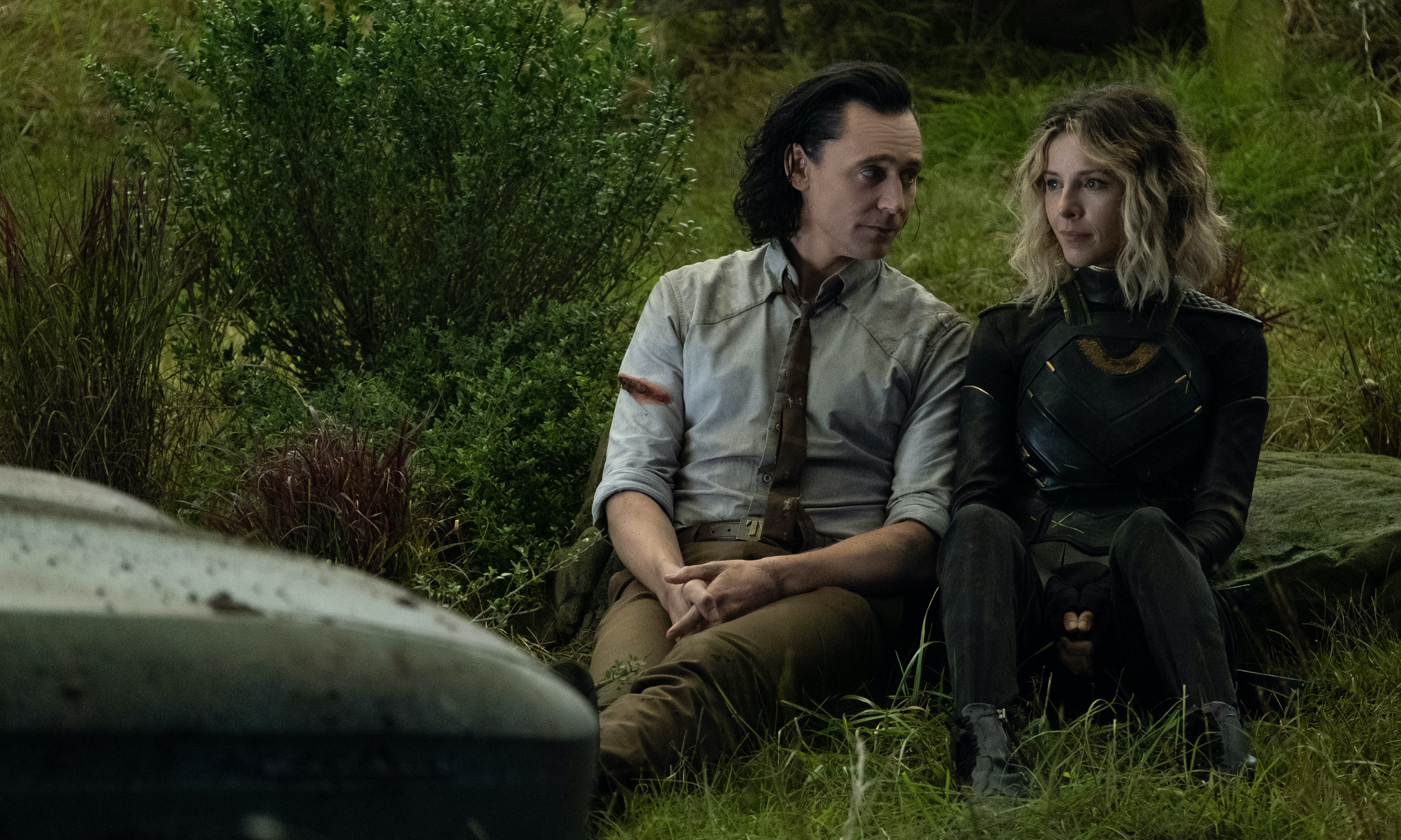 TomHiddleston and Sophia Di Martino sit side by side in the grass in Loki