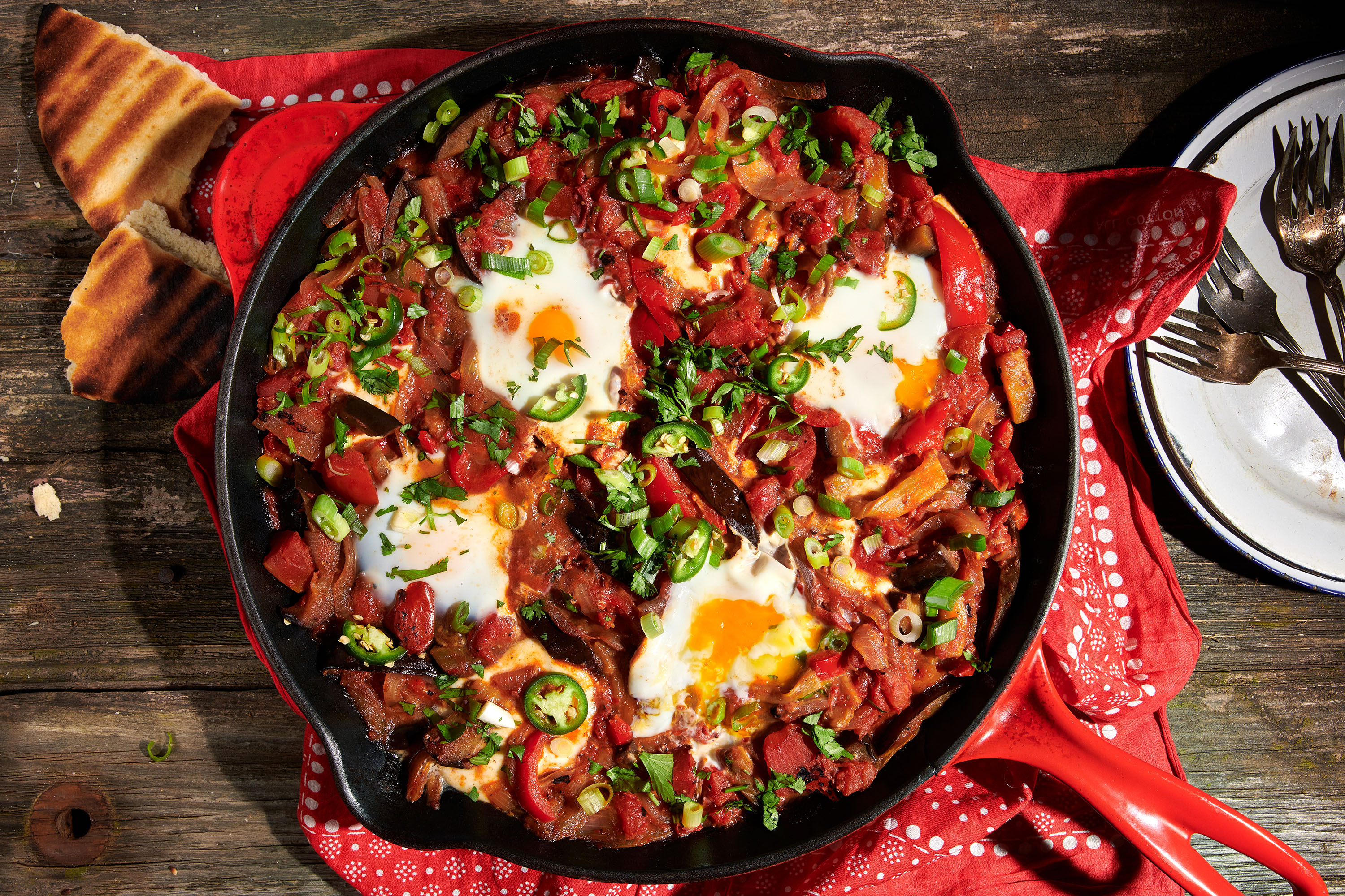 Shakshuka in a red cast-iron pan seen from above on a picnic table top, with a red bandana underneath.