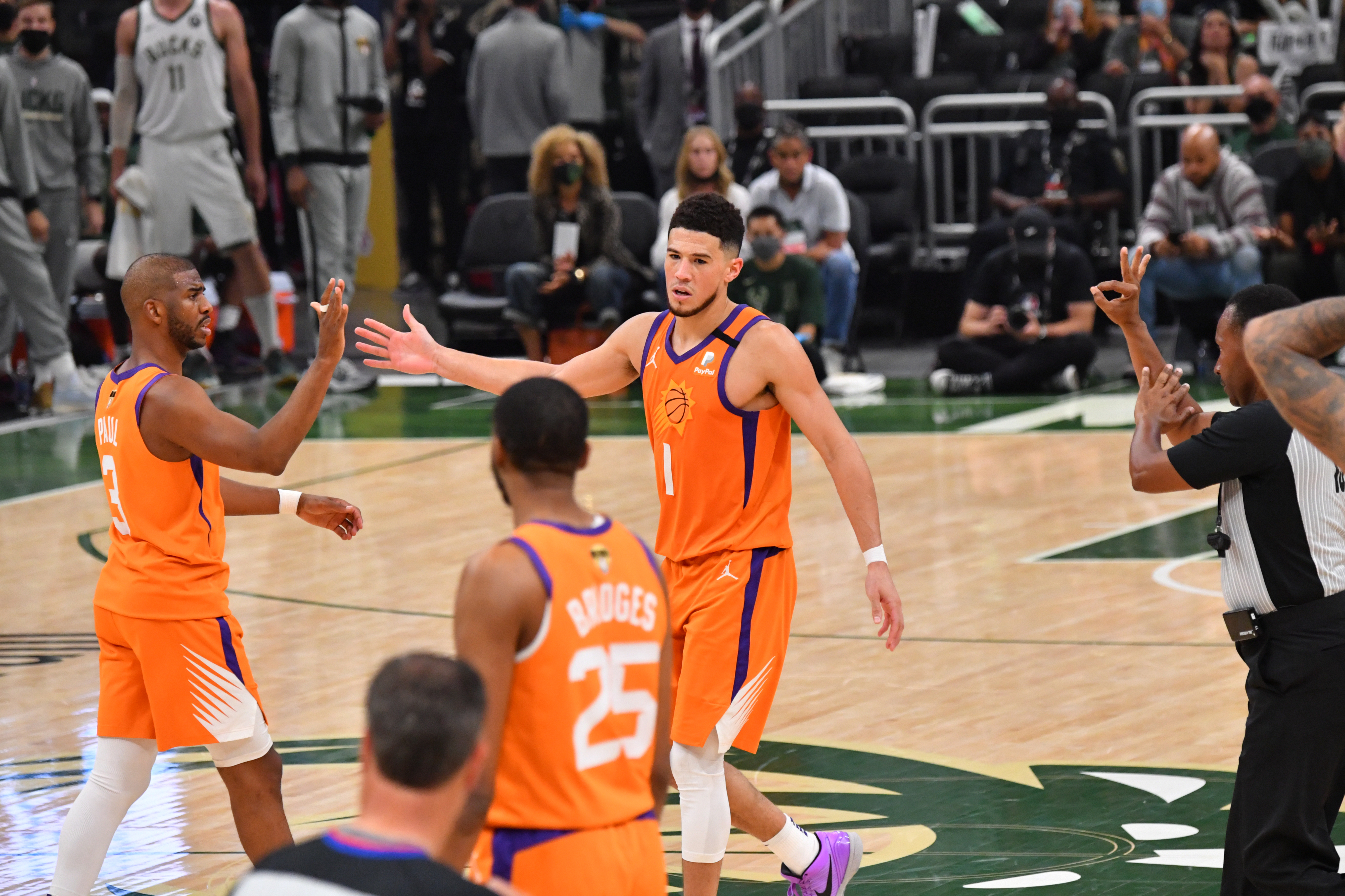 Chris Paul of the Phoenix Suns and Devin Booker of the Phoenix Suns high-five during Game Four of the 2021 NBA Finals on July 14, 2021 at Fiserv Forum in Milwaukee, Wisconsin.