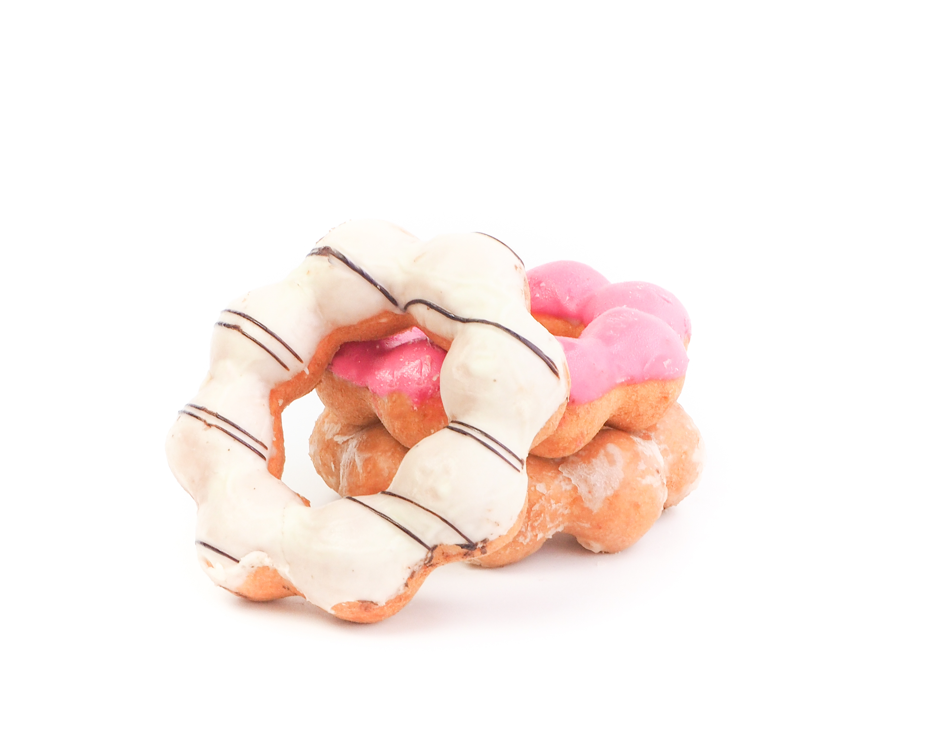 Two mochi doughnuts are stacked on each other and a third leans against the pile, all isolated on a white background. Each doughnut is frosted differently.