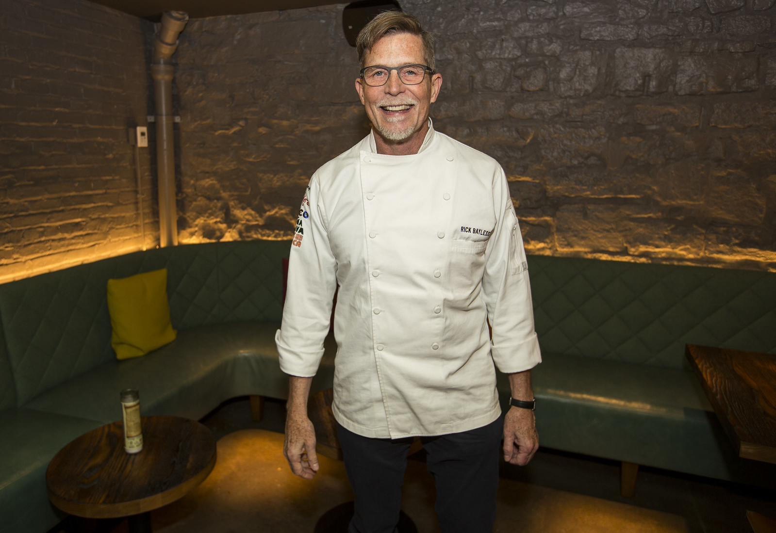 A smiling chef wearing a white chef's shirt.