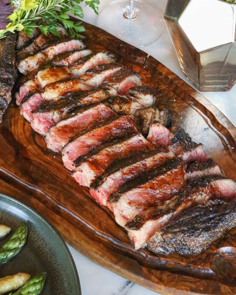 A steak sliced on a wooden cutting board