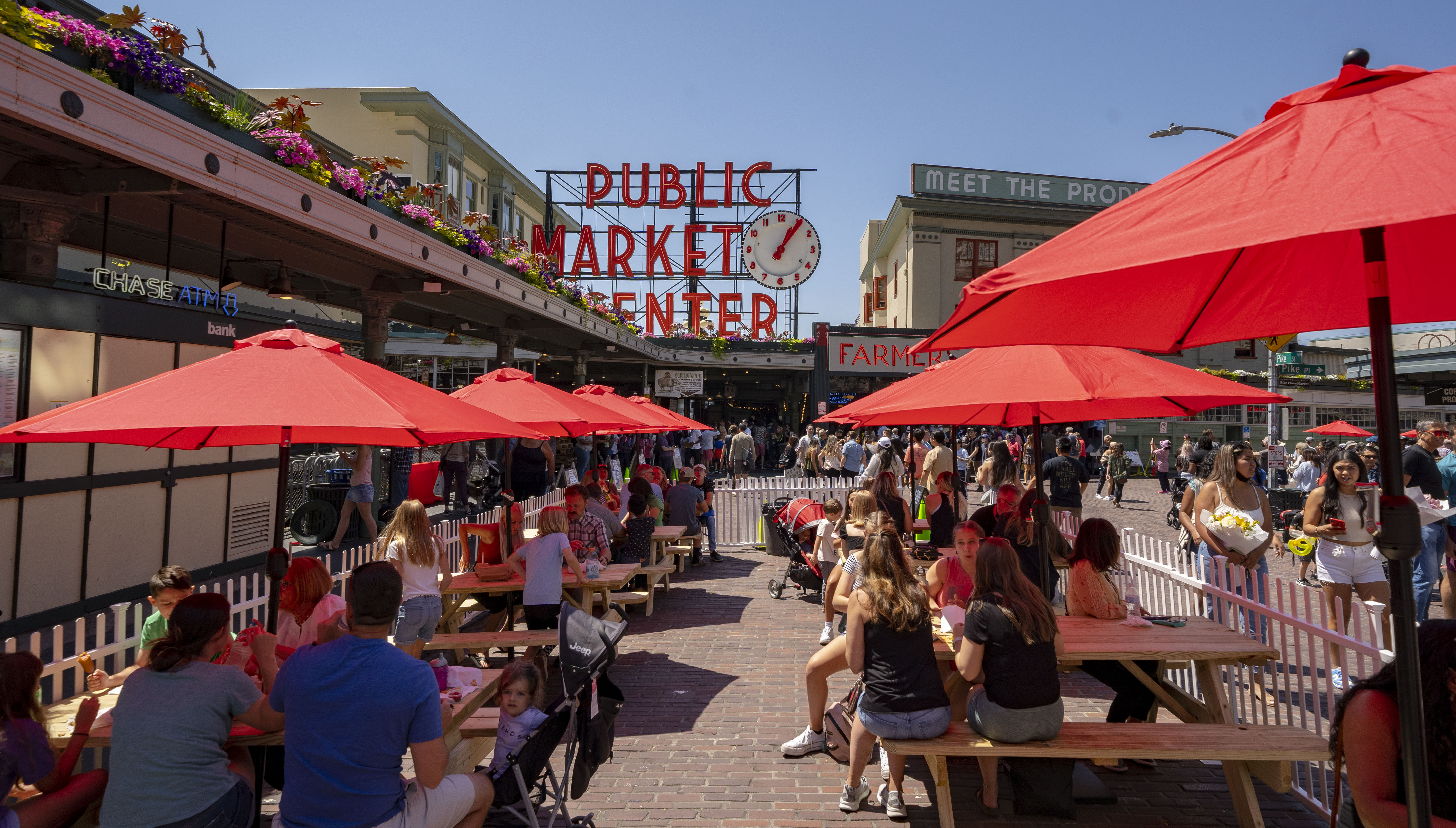 Red umbrellas cover picnic tables on the streets outside Pike Place Market, with the Market's famed clock and sign in the background.