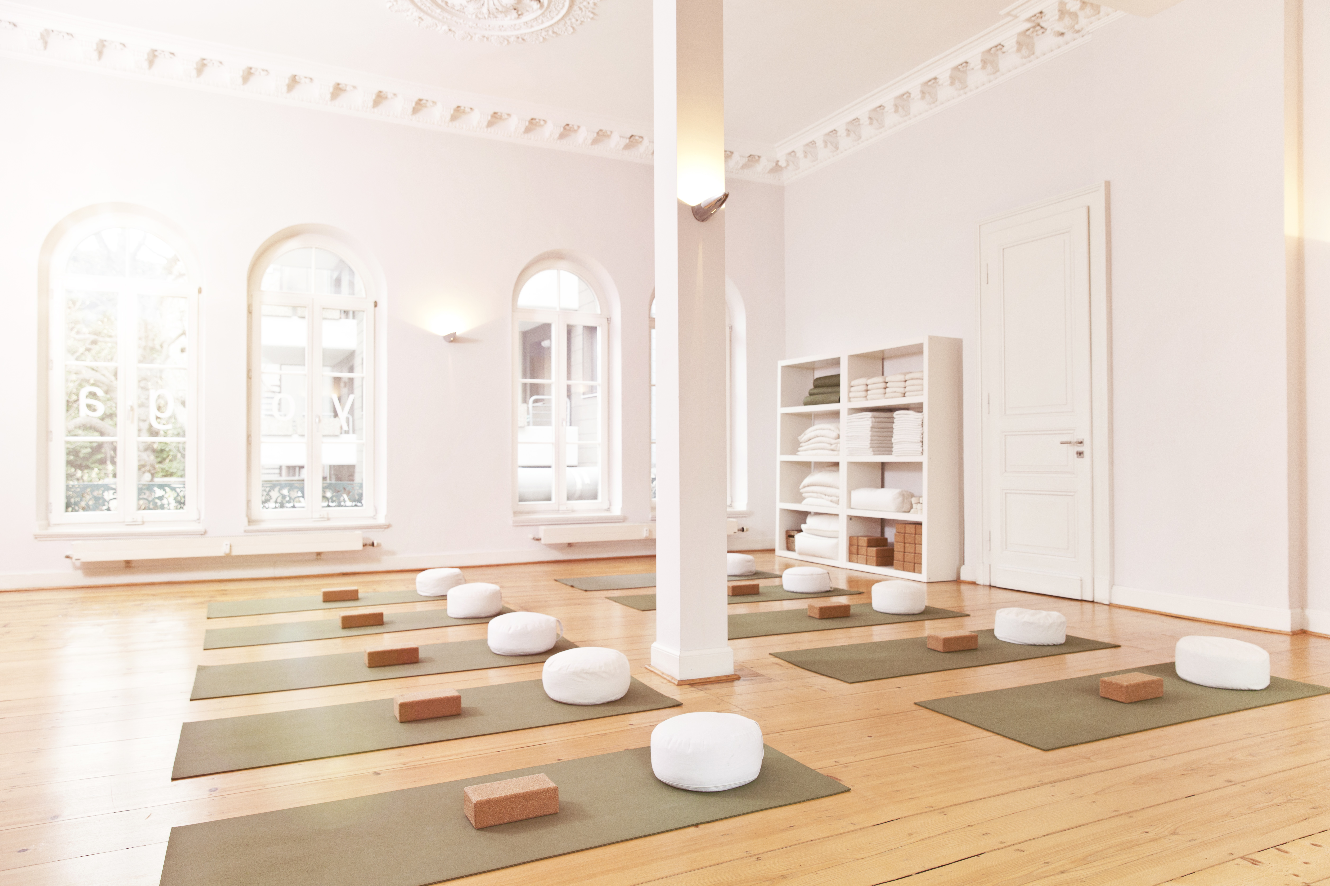 A spacious and empty yoga studio with mats laid out.