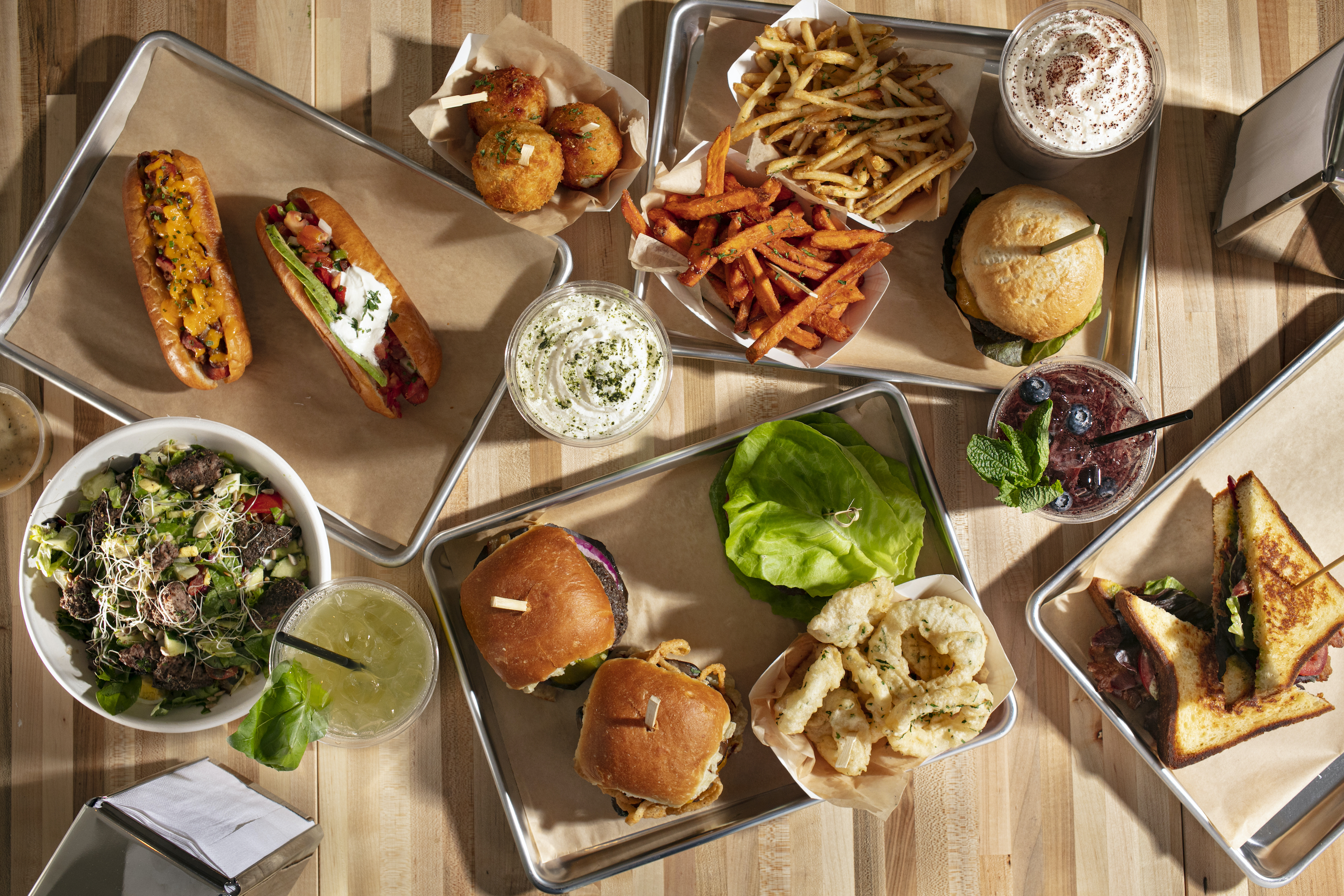 An overhead photograph of metal trays lined with food, including hot dogs, salads, burgers, onion rings, and fries