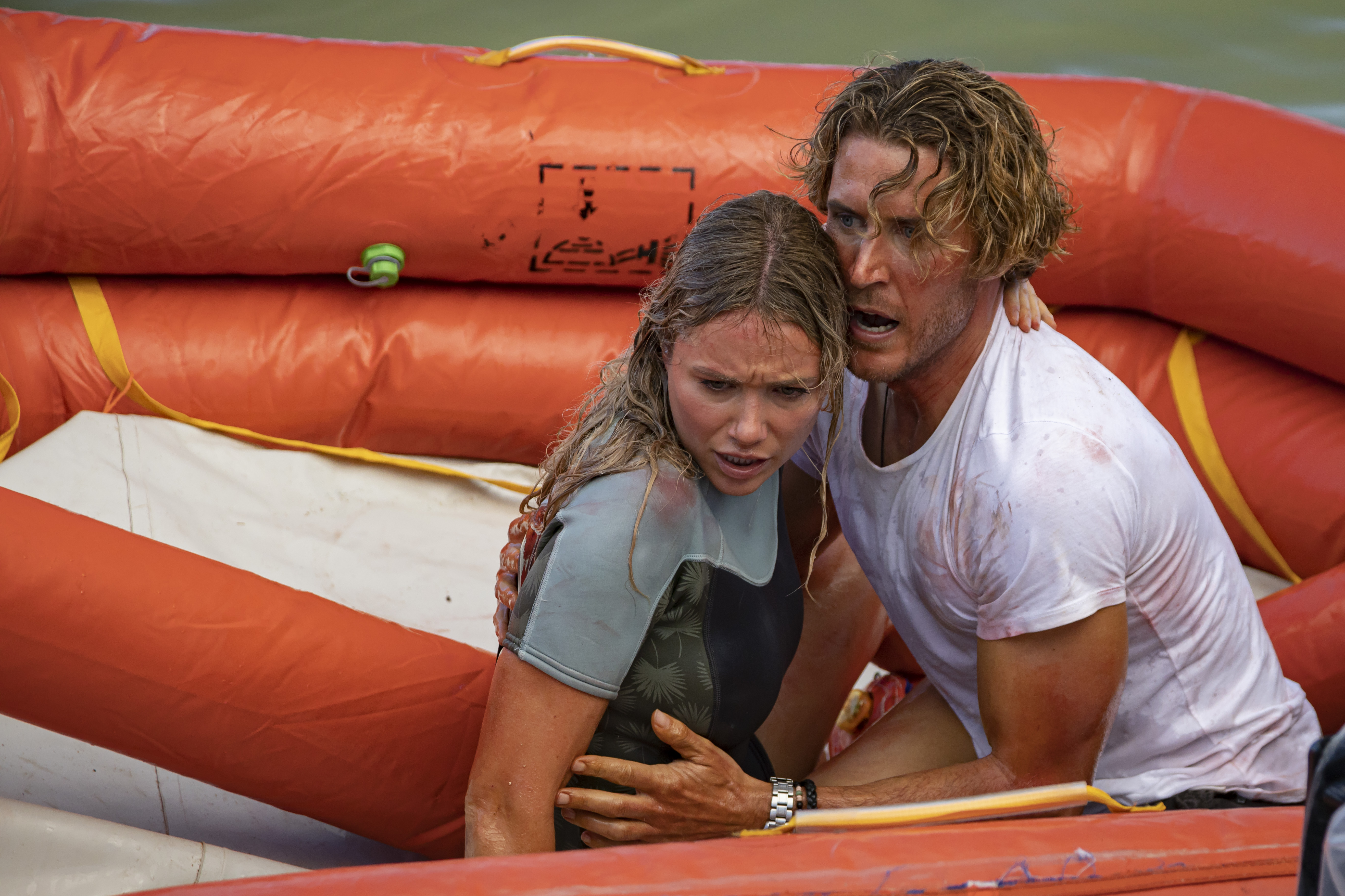 Katrina Bowden and Aaron Jakubenko clutch each other in terror in a lifeboat in Great White