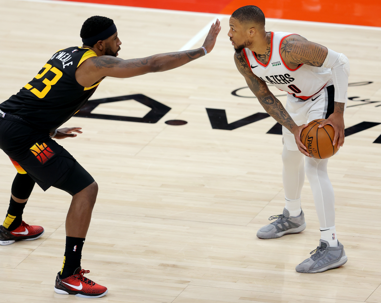 Utah Jazz forward Royce O'Neale (23) sticks his hand in front of Portland Trail Blazers guard Damian Lillard (0)
