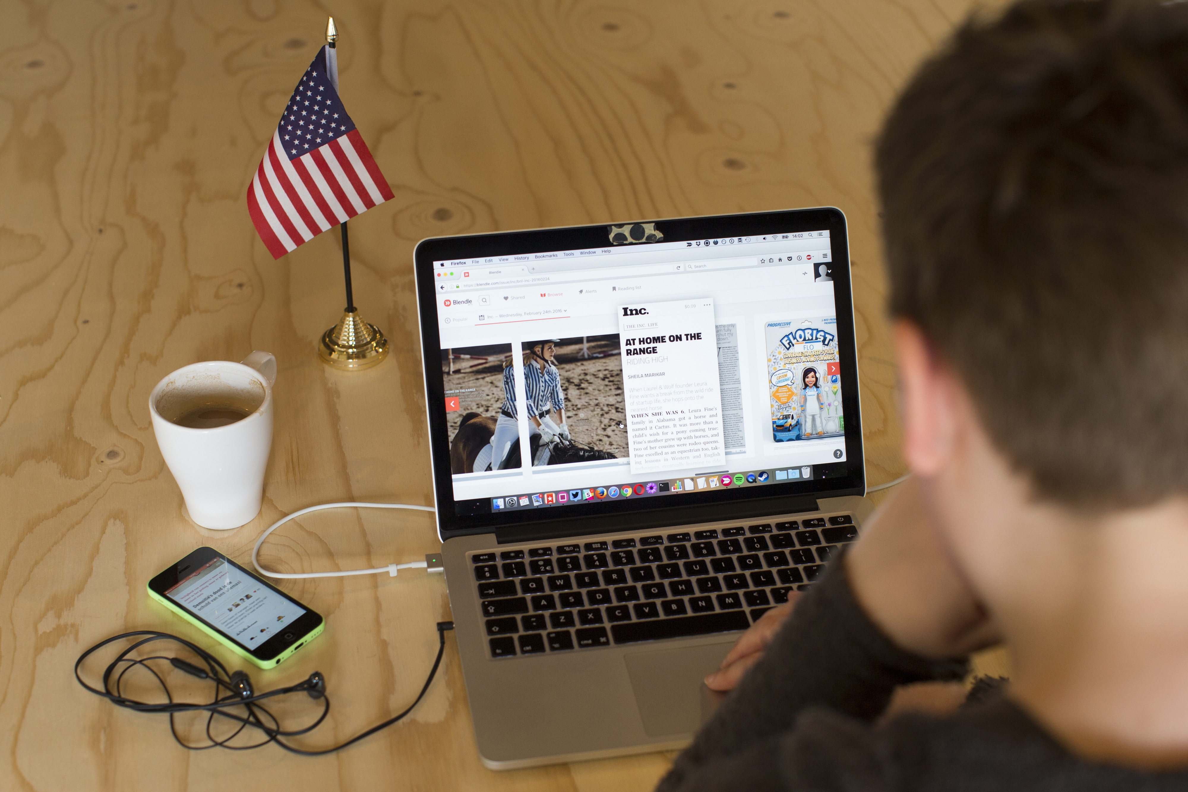 A person sits at a table with an open laptop computer, a phone plugged into it, a cup of coffee, and a small American flag on a self-standing stick.