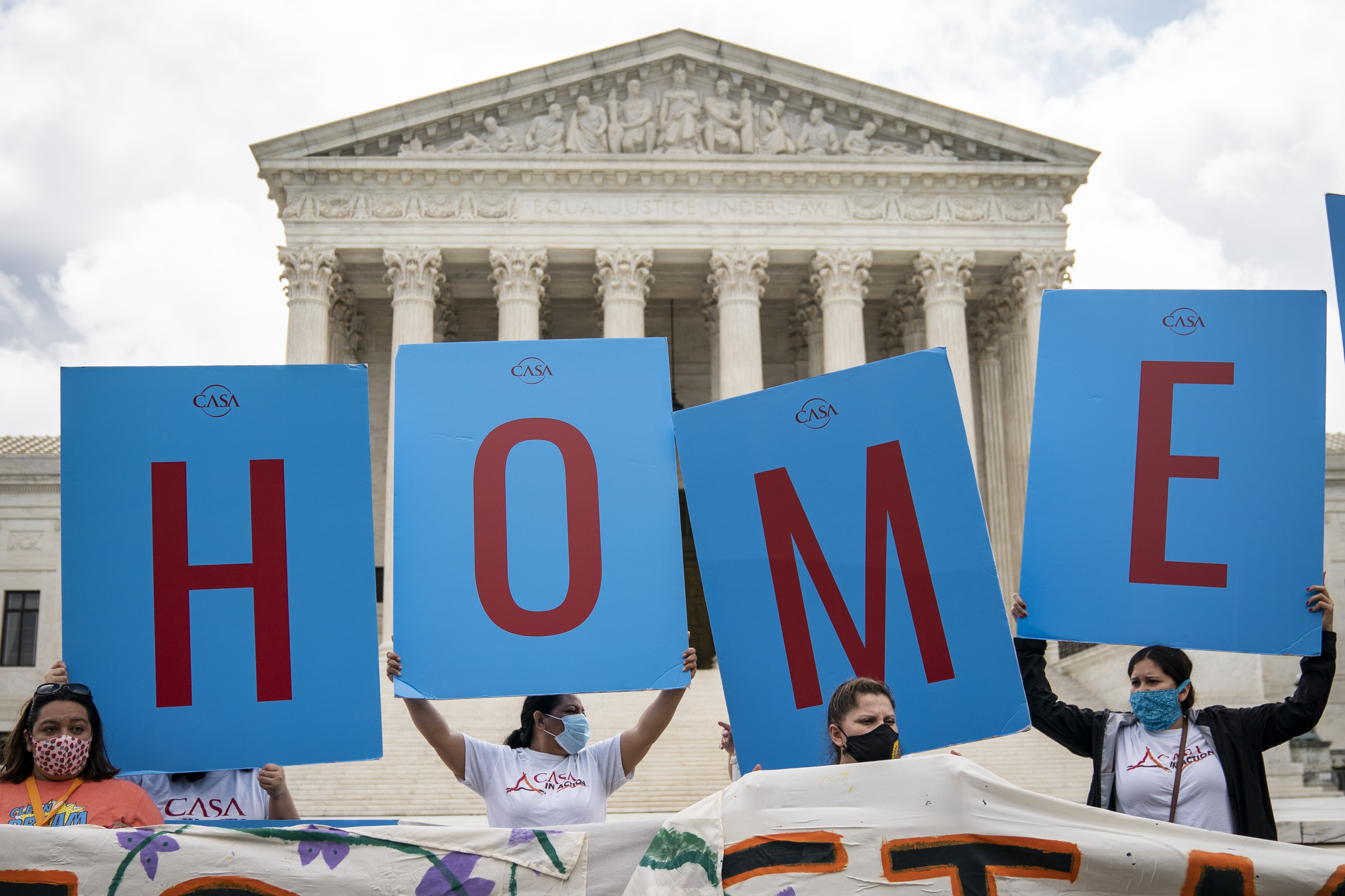DACA recipients and their supporters rally outside the US Supreme Court on June 18, 2020 in Washington, DC. A group of individuals are holding large signs that spell home.