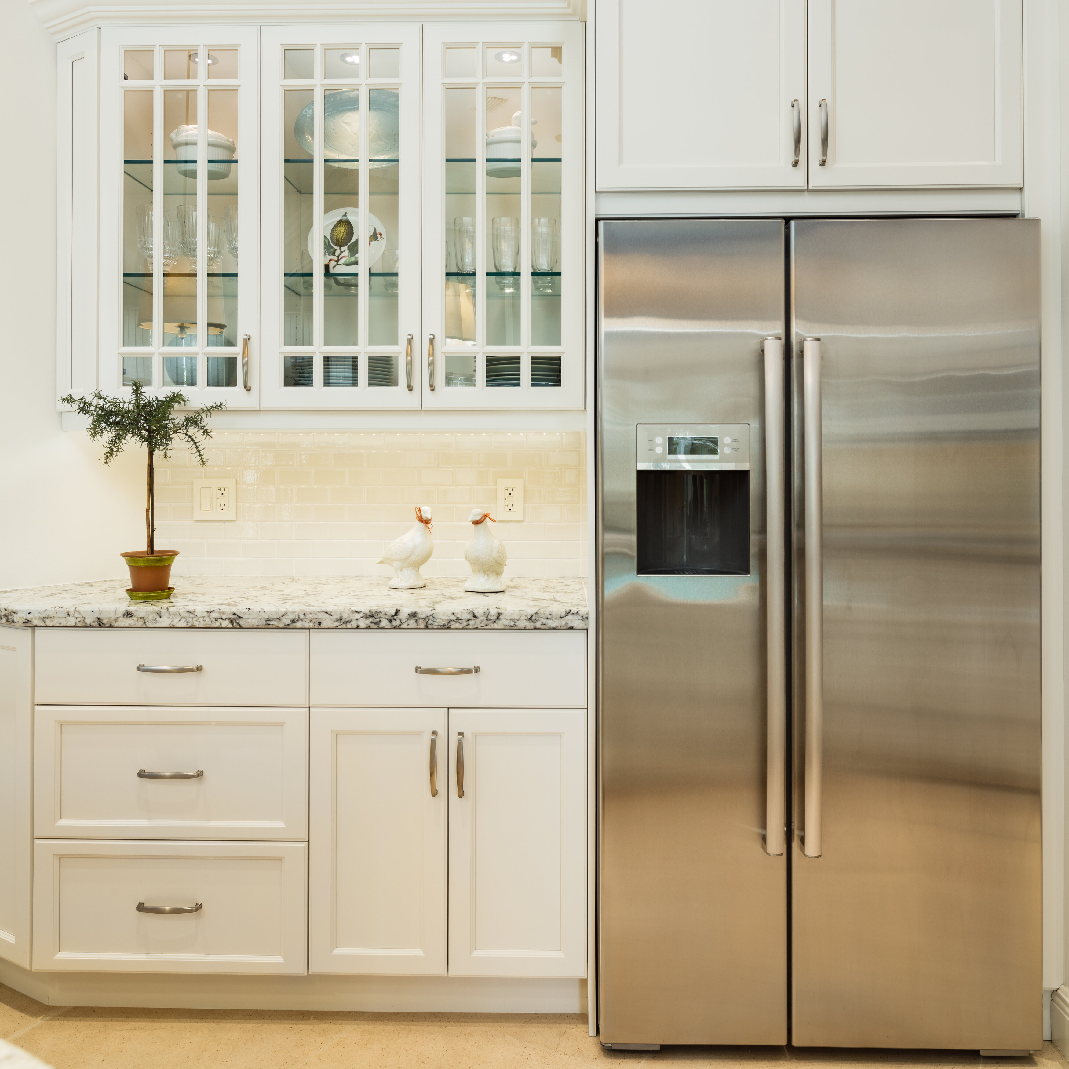 A stainless steel refrigerator near a countertop with decorative plant.
