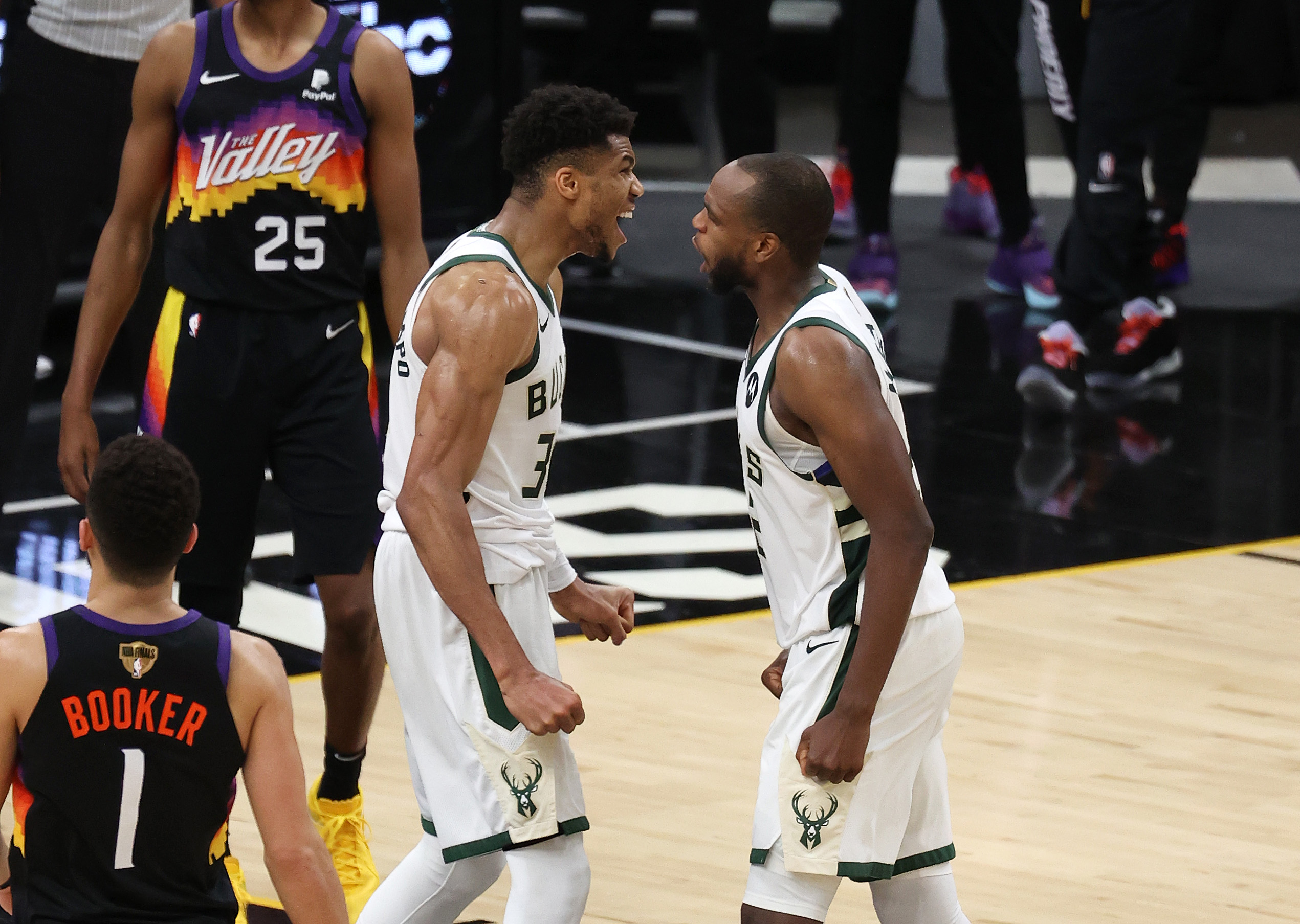 Giannis Antetokounmpo and Khris Middleton of the Milwaukee Bucks celebrate a win against the Phoenix Suns in Game Five of the NBA Finals at Footprint Center on July 17, 2021 in Phoenix, Arizona.