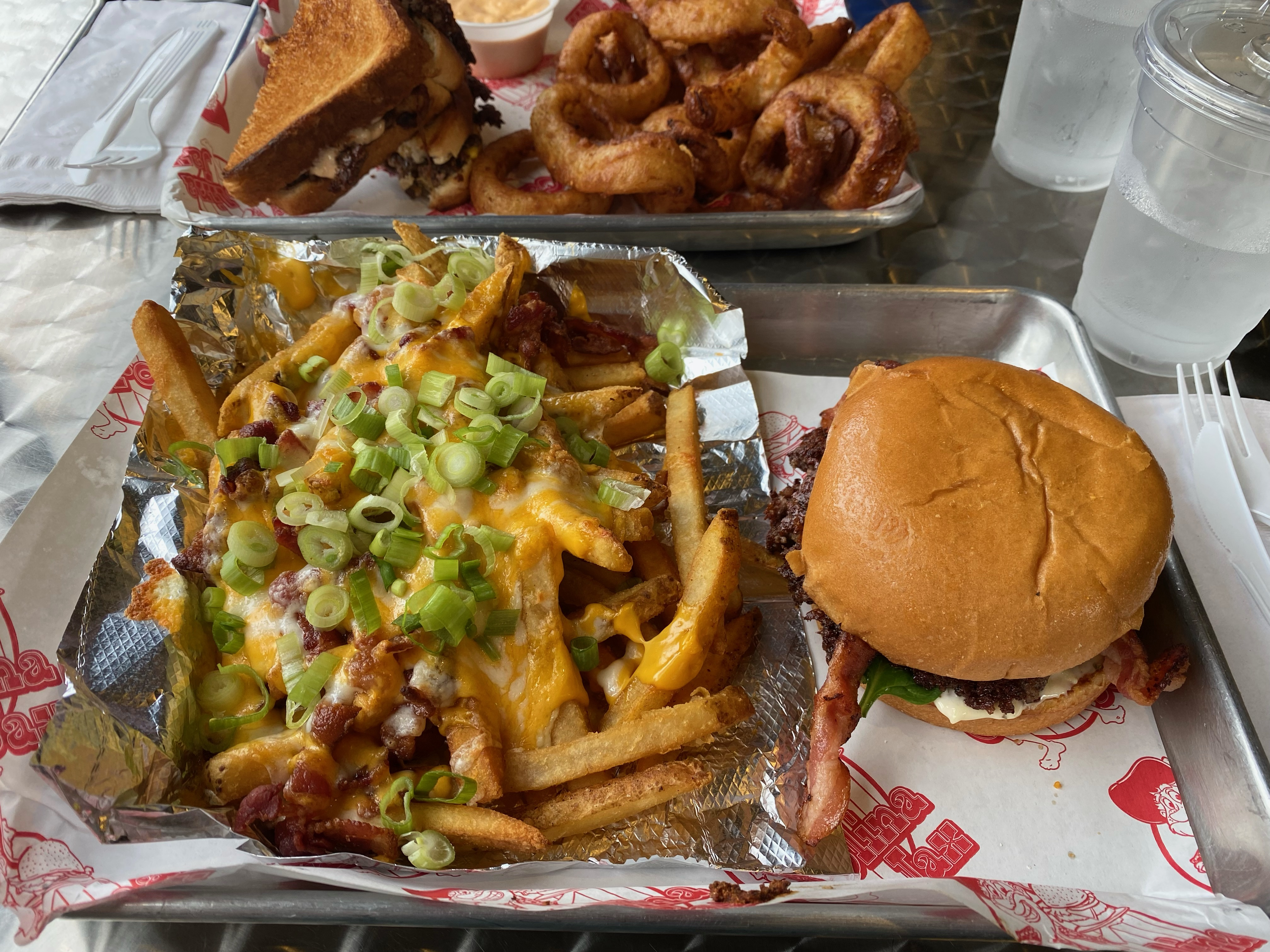 Burger and loaded cheese fries on a tray