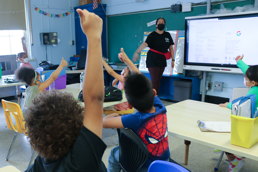 Young students raise their hands and give a thumbs up at their teacher during a summer program.