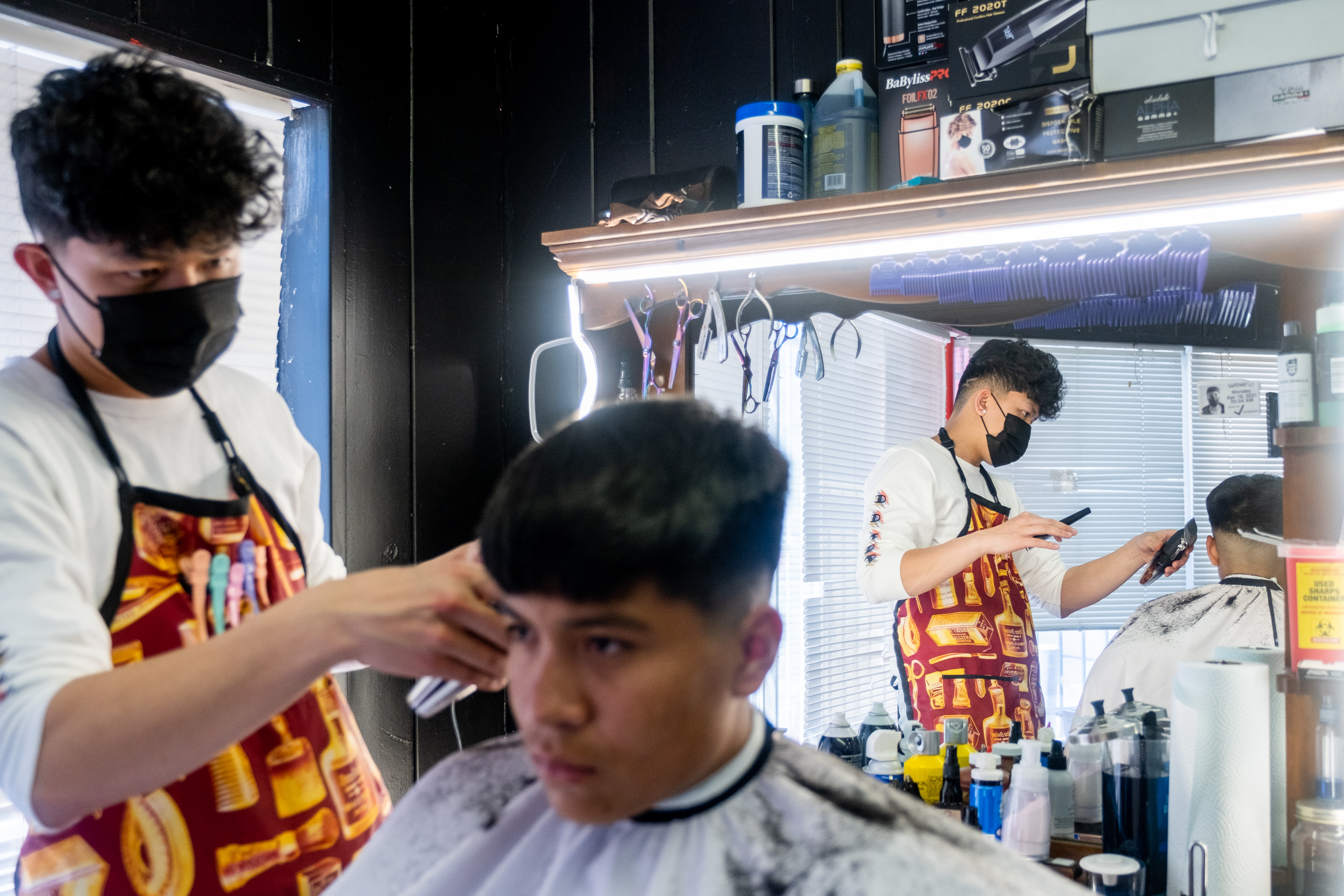 A young man wearing a black mask and barber's apron cuts the hair of another young man in a barber shop. The barber is reflected in his mirror, adorned with bright lights at the top.