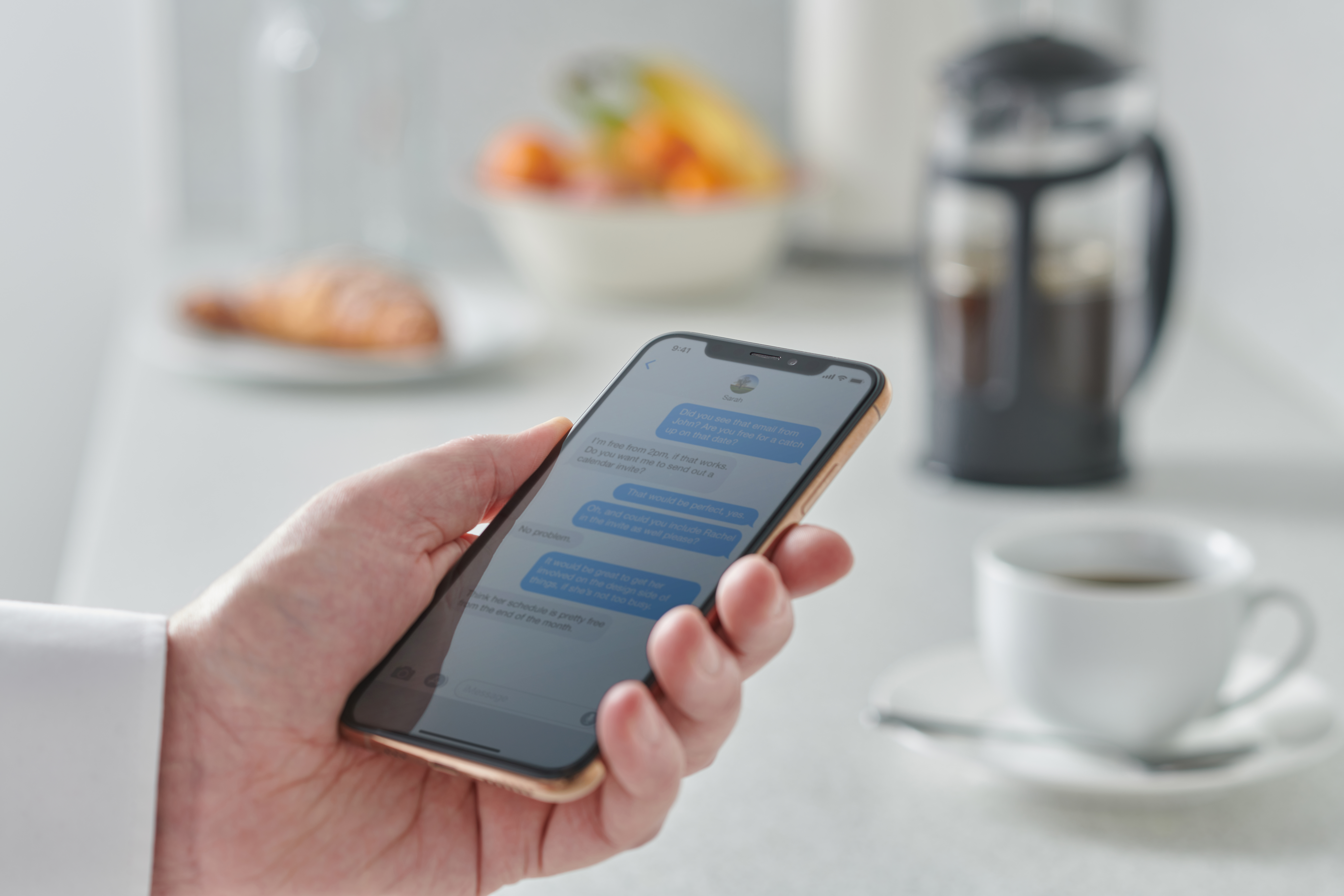 A hand holding a smartphone displaying iMessage. A table with coffee and fruit is visible in the background.