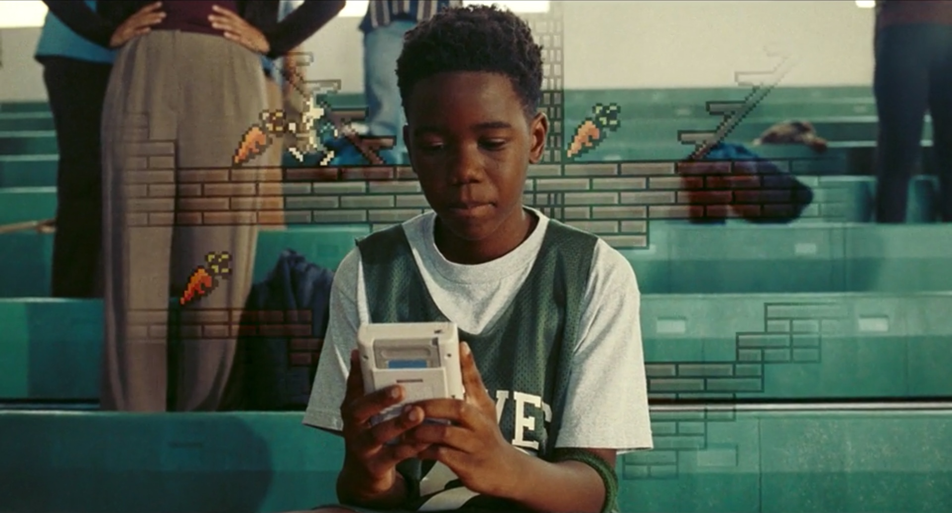 Young LeBron James plays a Game Boy in a still from Space Jam: A New Legacy