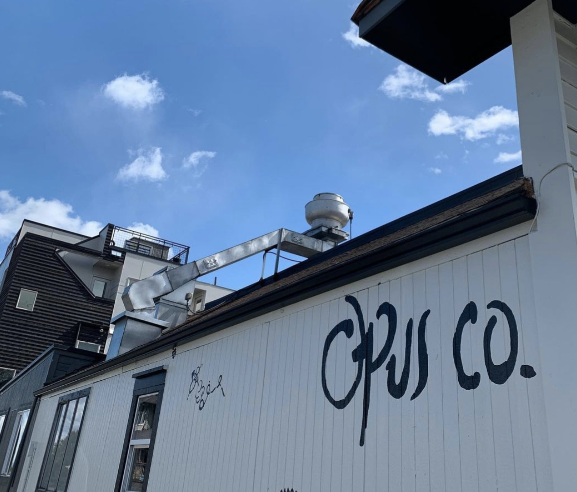 The exterior of Opus Co. on a clear day, with the restaurant's name scrawled in blue lettering on the side of the building
