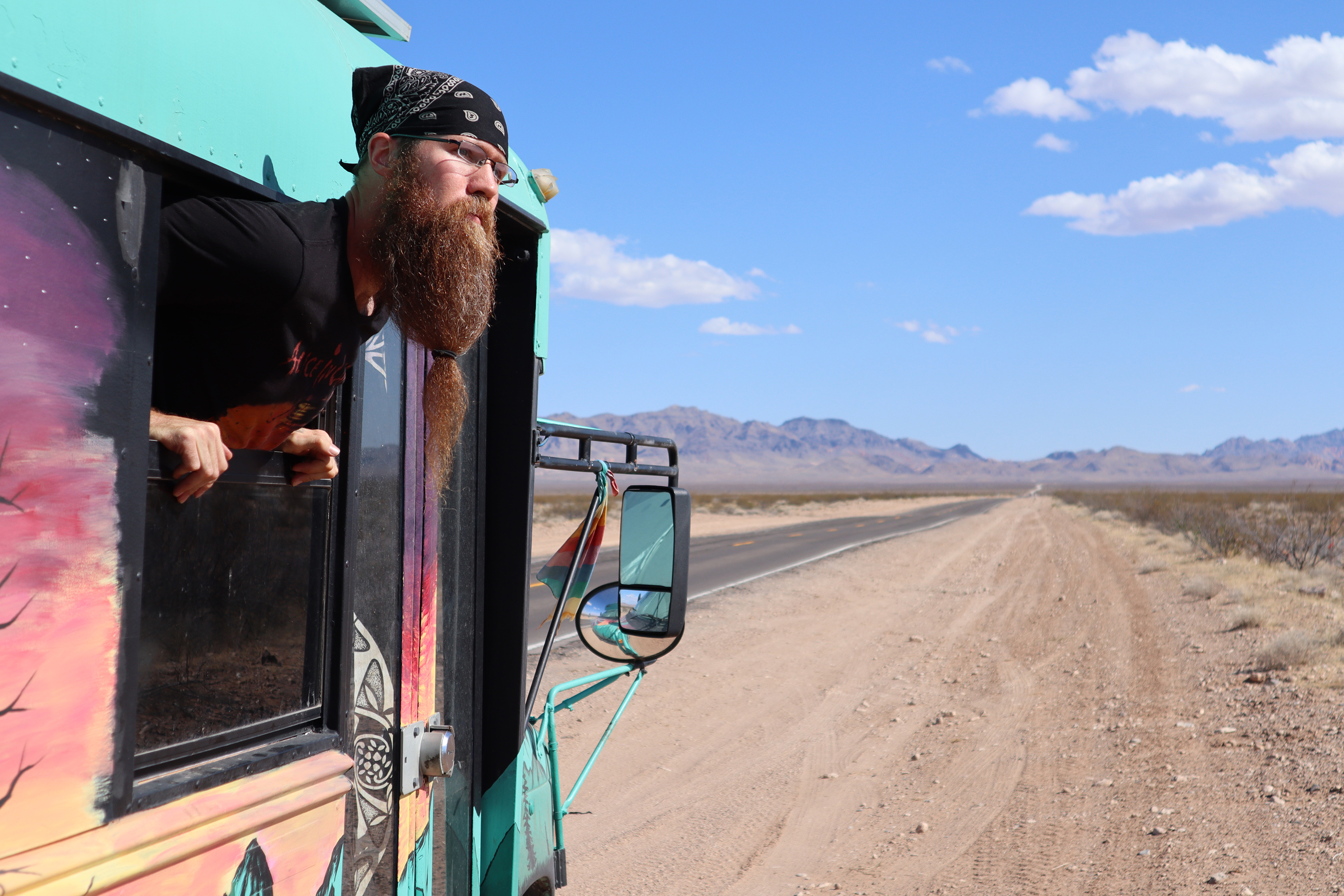 Luke Brokaw looks out the window of the converted school bus that he lives in while working remotely.