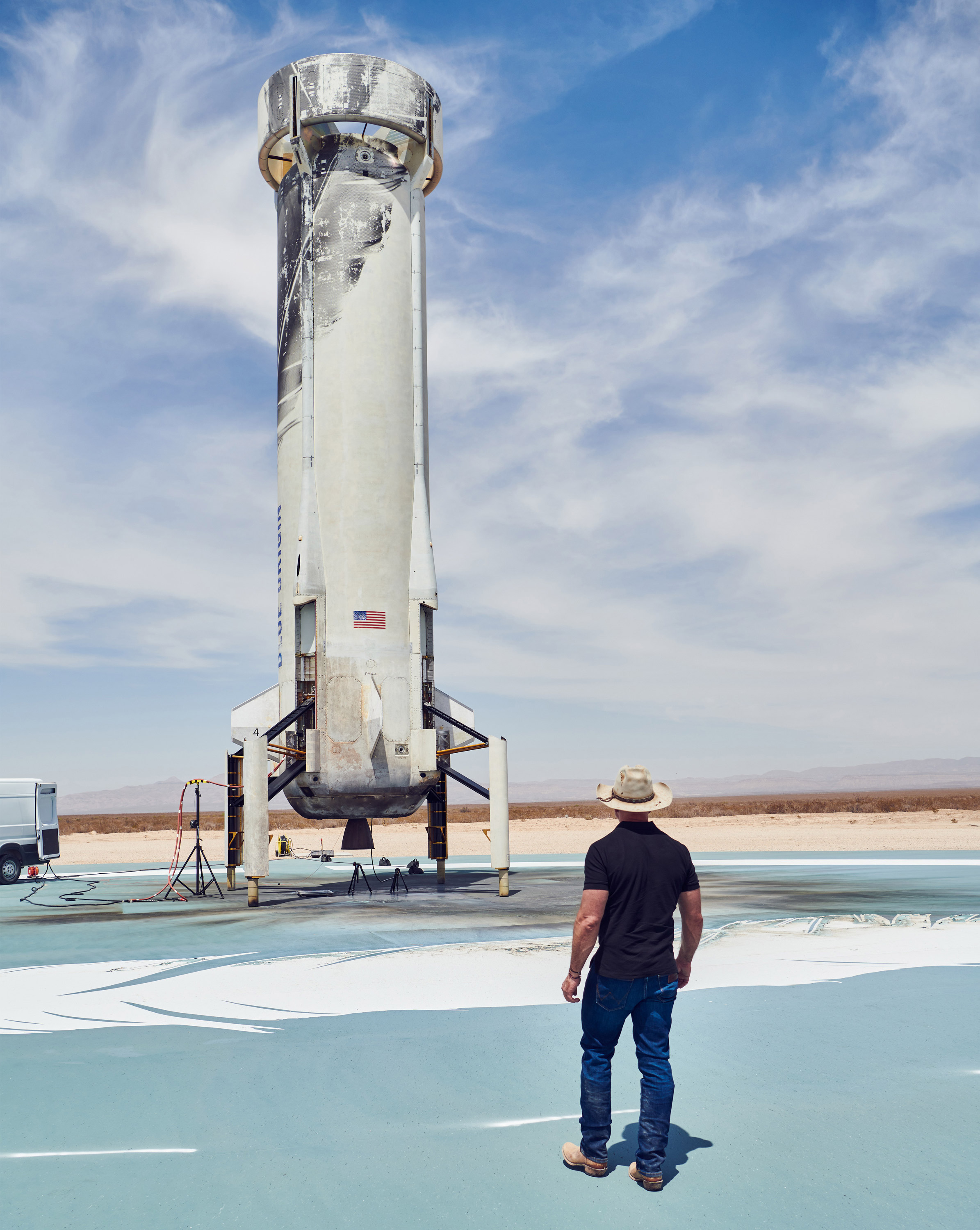 Jeff Bezos stands looking at the Blue Origin rocket on its launchpad.