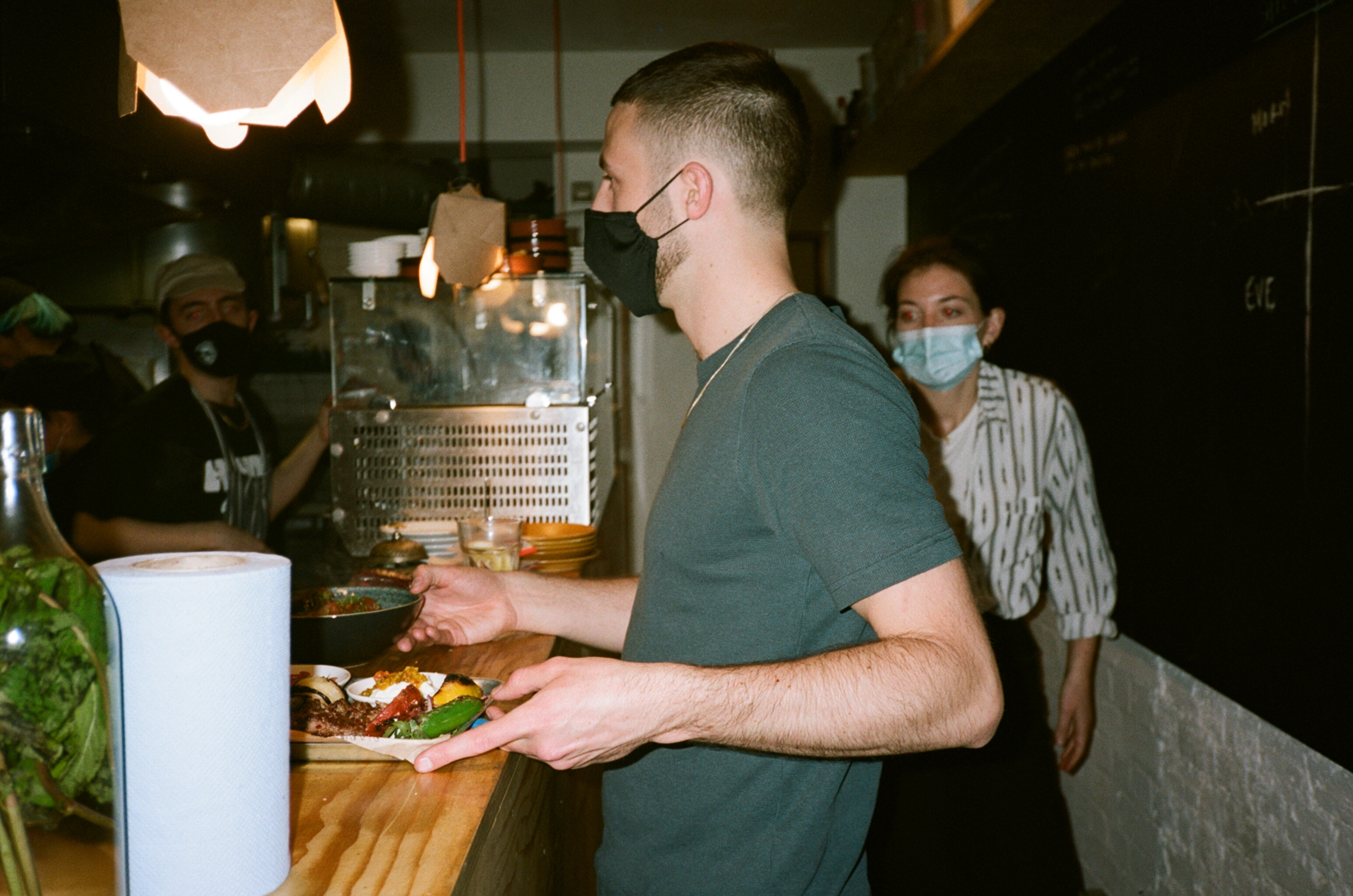 Wait staff prepare to run dishes to guests indoors at Nandine in Camberwell