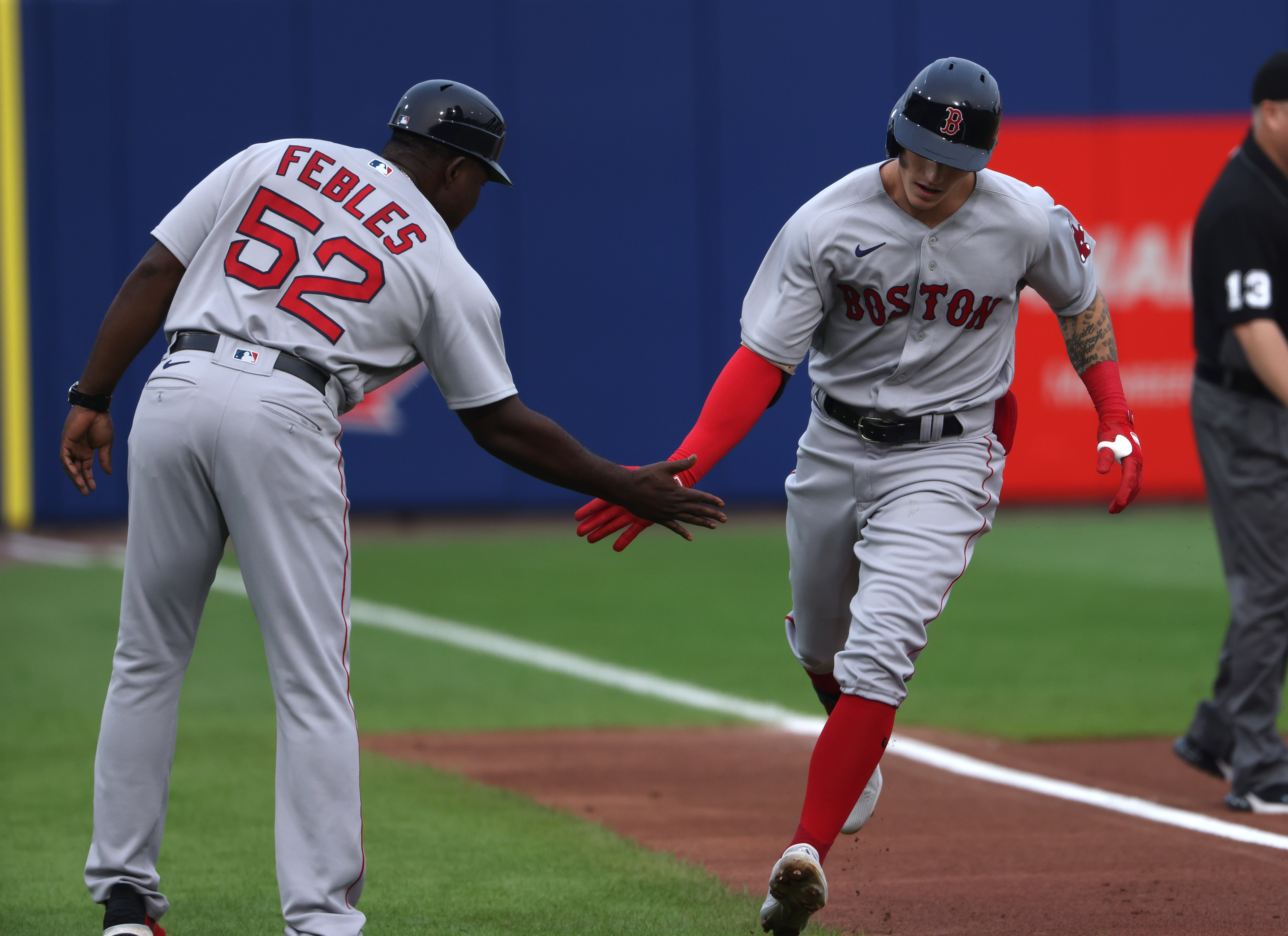 Boston Red Sox center fielder Jarren Duran (40) celebrates his home run with third base coach Carlos Febles (52) during the first inning against Toronto Blue Jays at Sahlen Field.