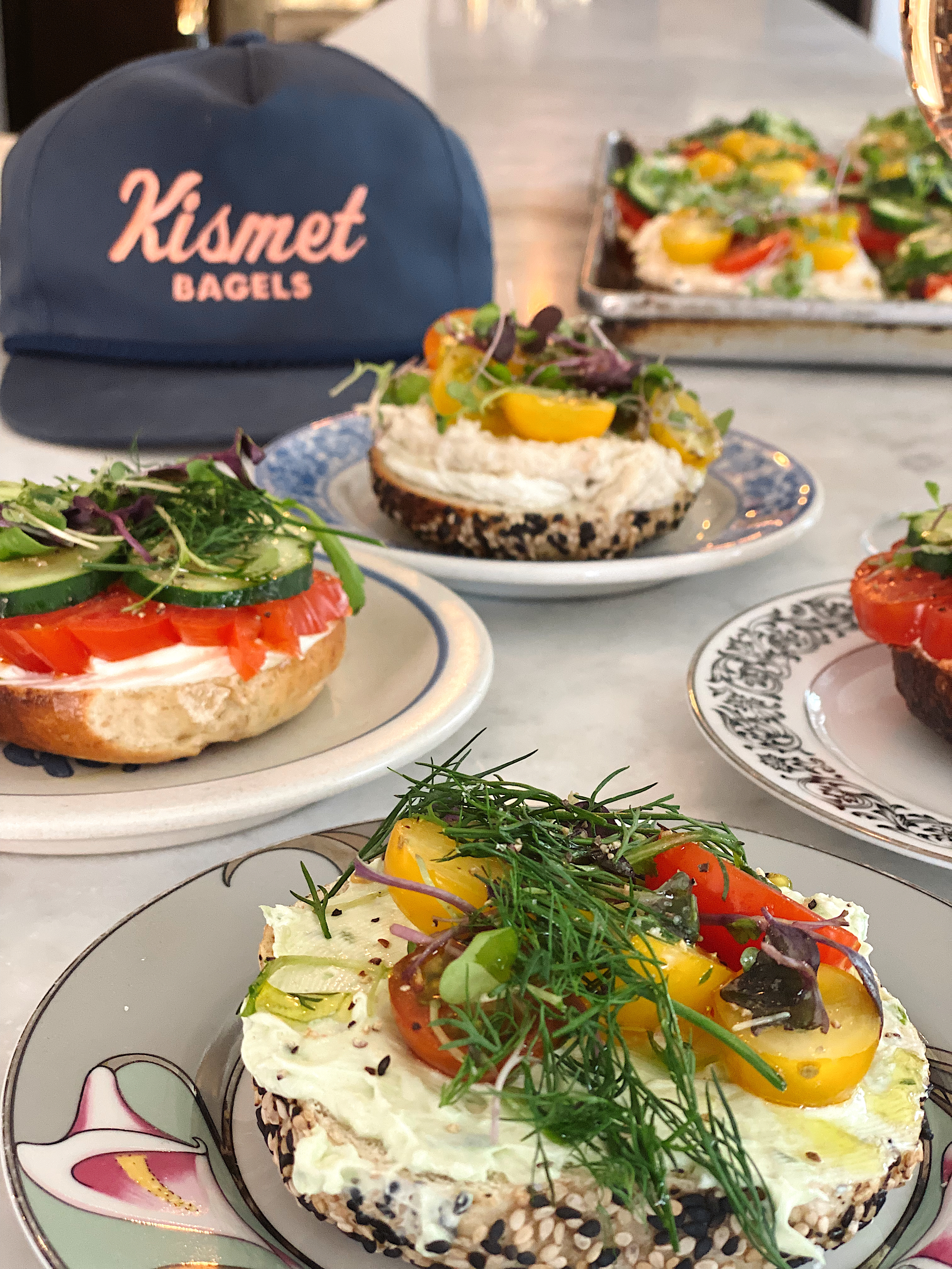 three different open-faced bagels with a kismet bagels hat in the background