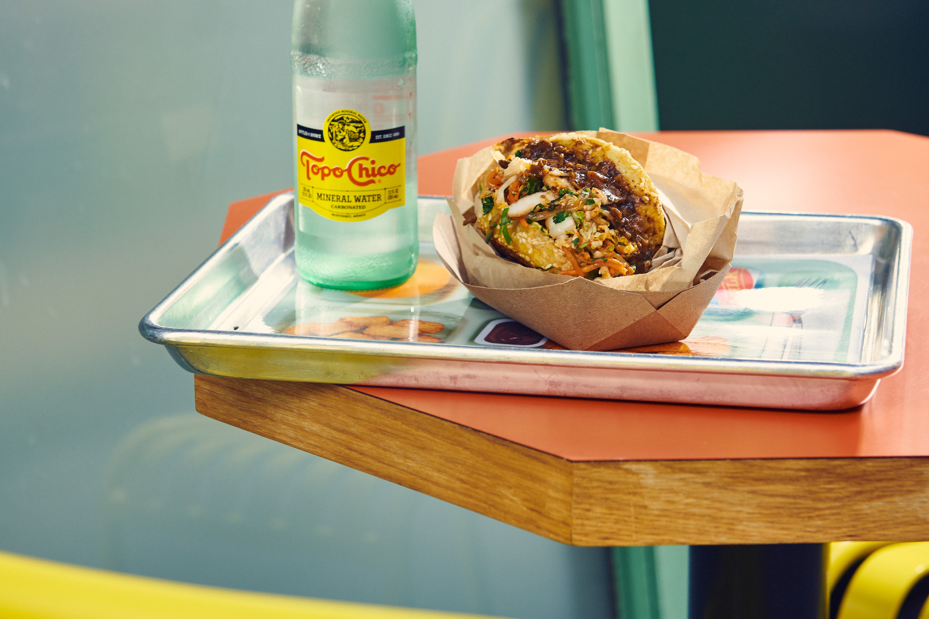 A mushroom Sloppy Joe is shot from the side; it sits on a metal lunch tray on an orange table; a bottle of Topo Chico stands next to the sandwich