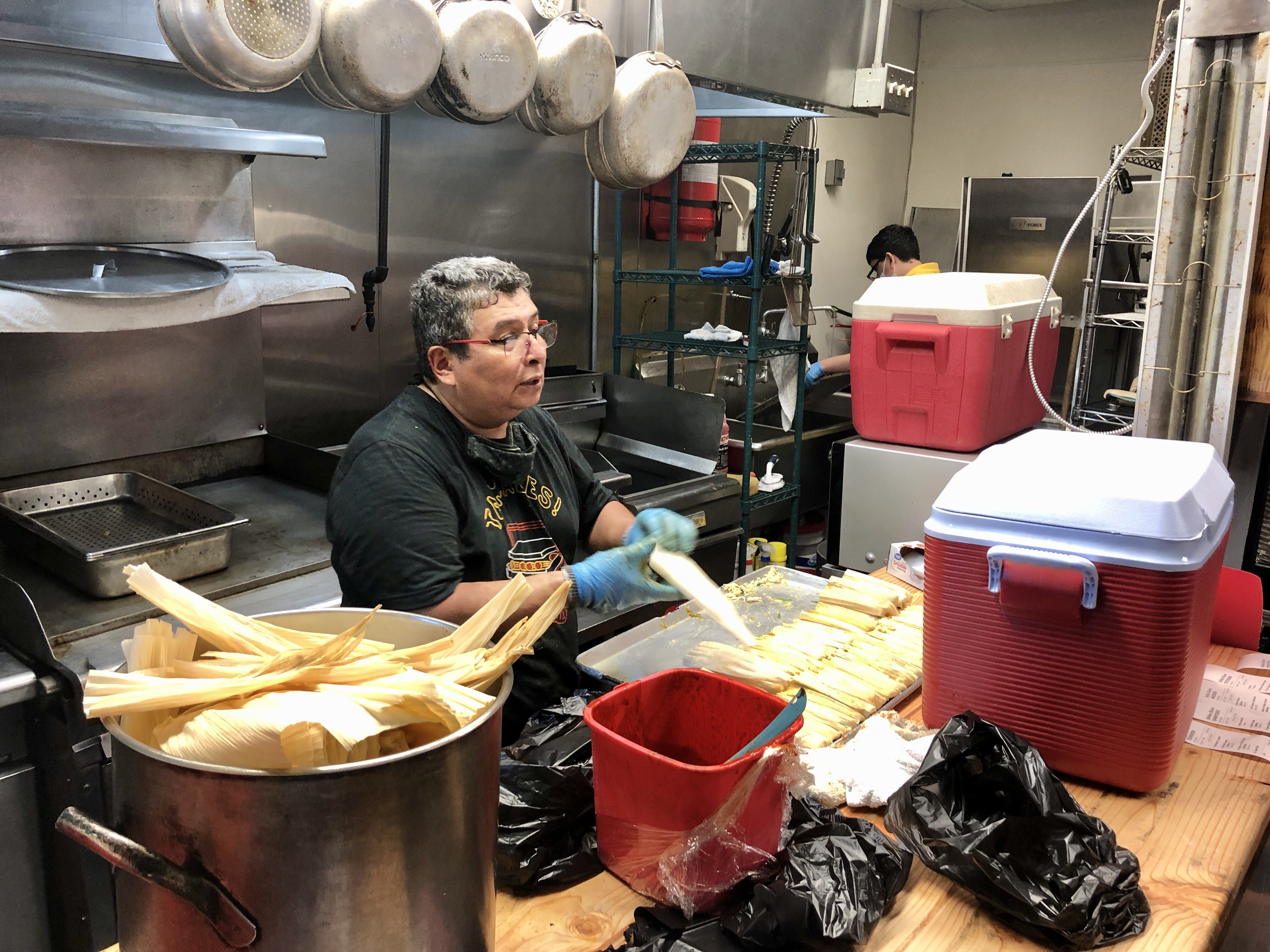 A man making tamales in a kitchen.