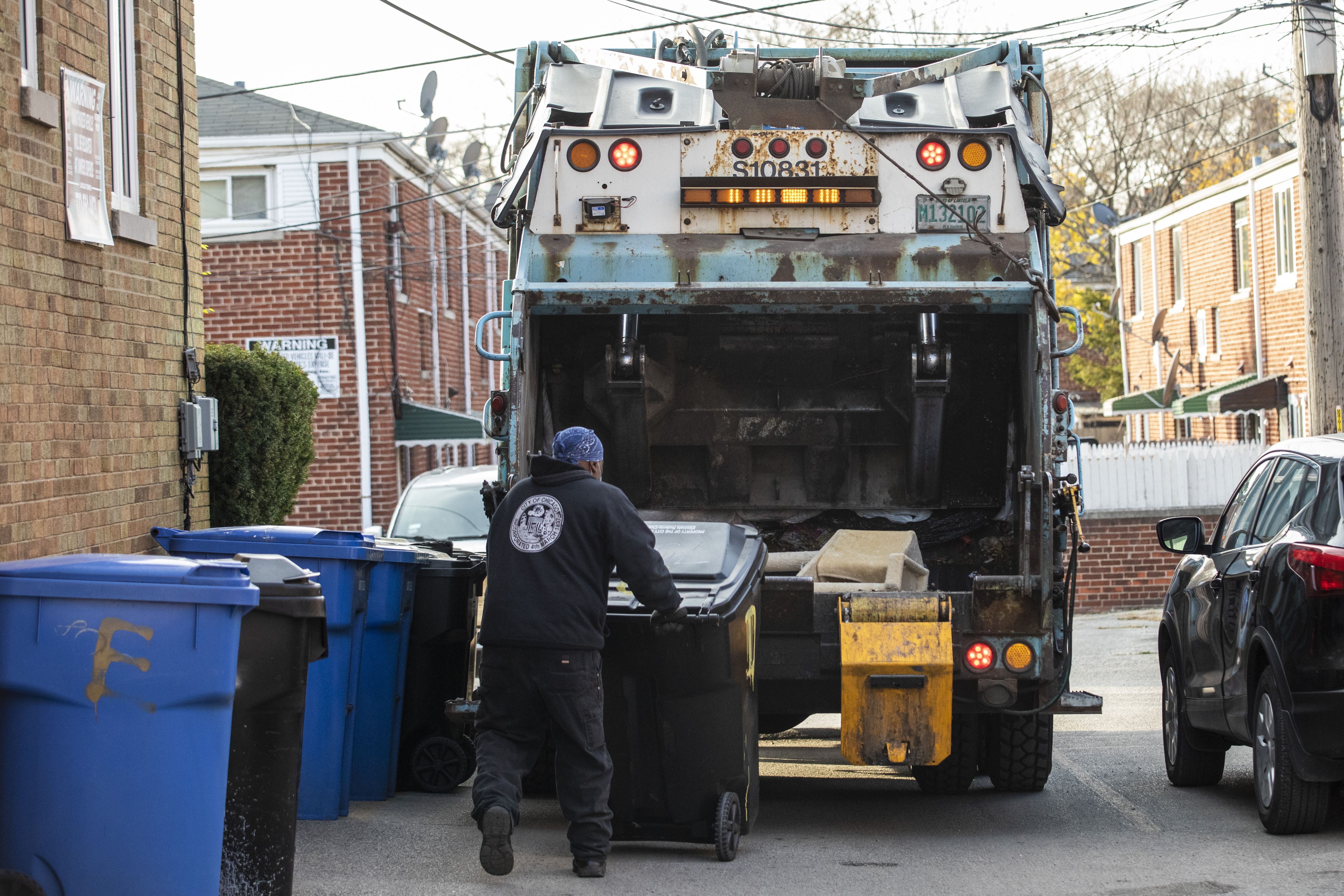 A worker with the city's Department of Streets and Sanitation loads a garbage truck in the 7500 block of North Ridge Boulevard in Rogers Park
